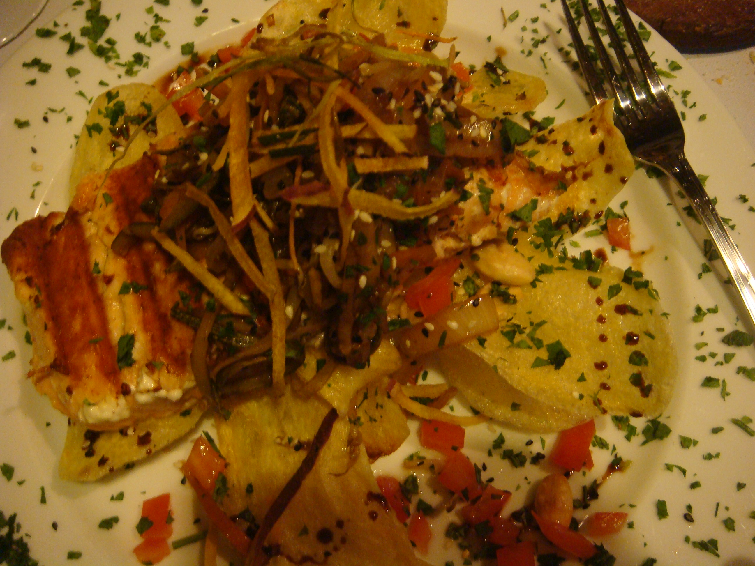 Grilled salmon and crispy potato slices, garnished with sauteed vegetables