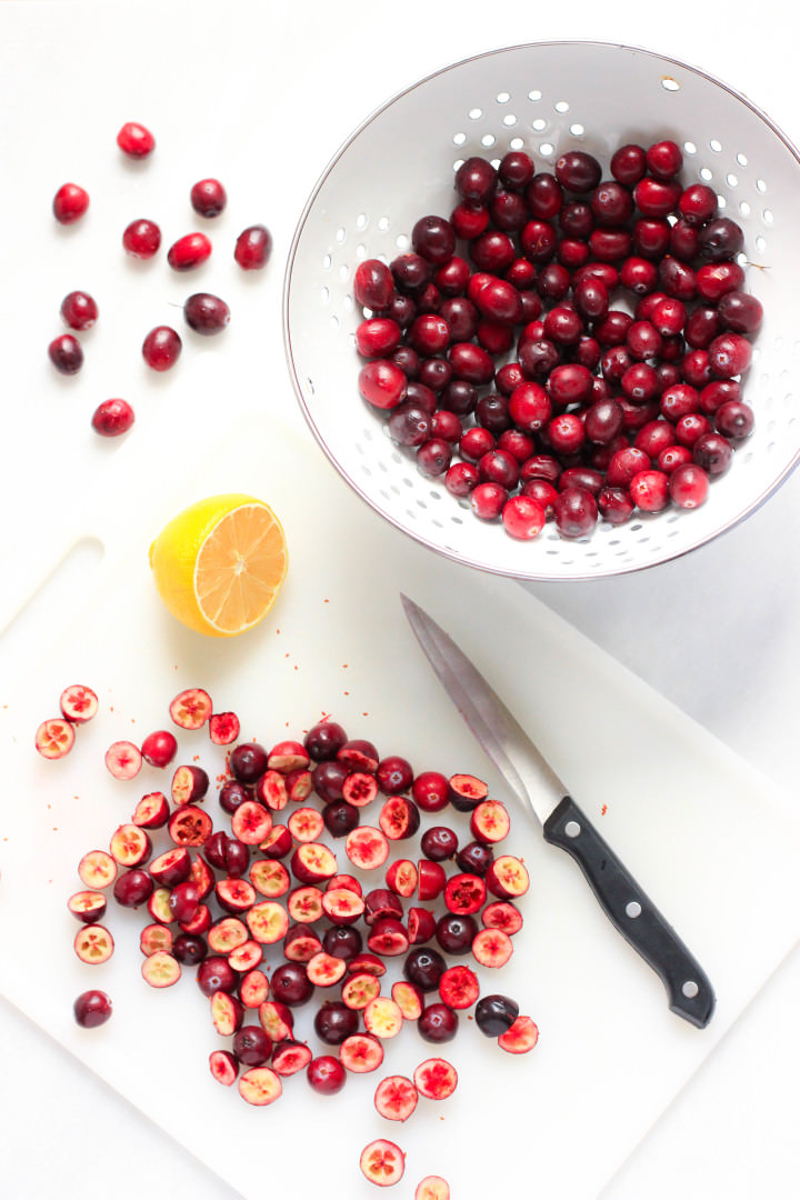 Fresh cranberries cut into halves on a chopping board.