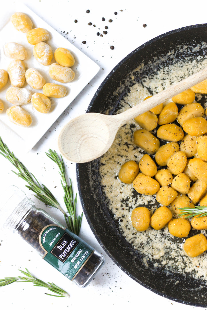 A pan of cooked pumpkin gnocchi in sauce.