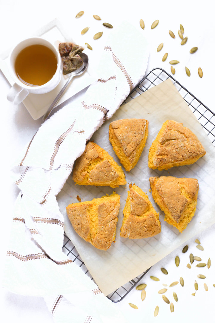 Top down shot of pumpkin scones, a cup of tea and a kitchen towel.