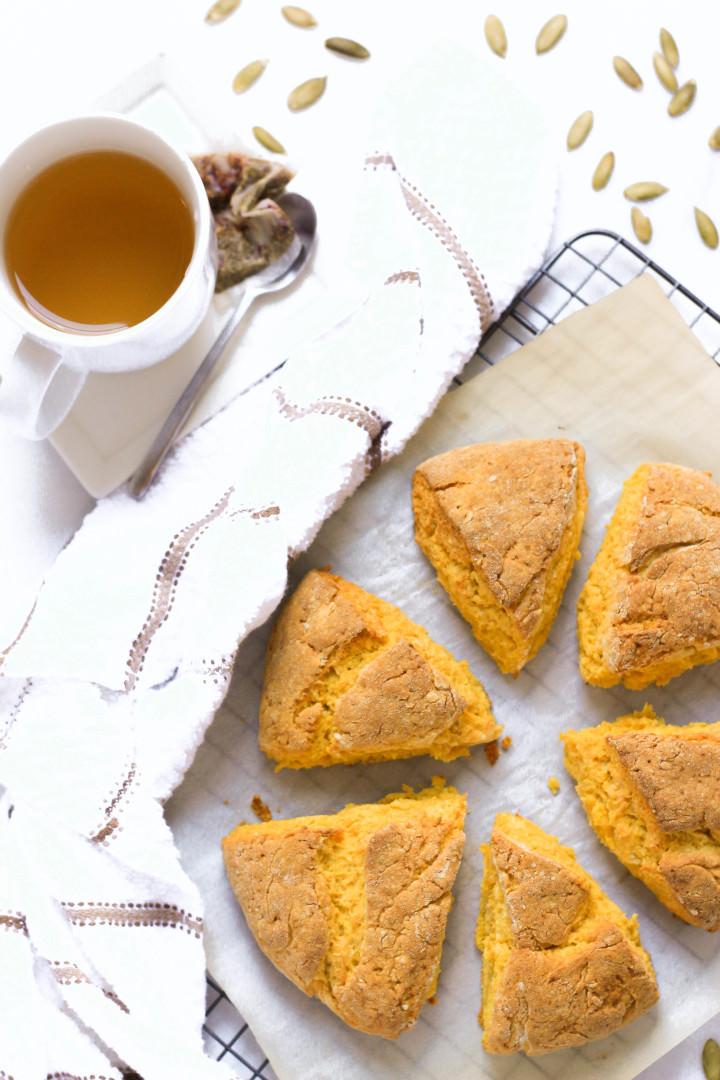Freshly baked scones on parchment paper alongside a mug of tea.