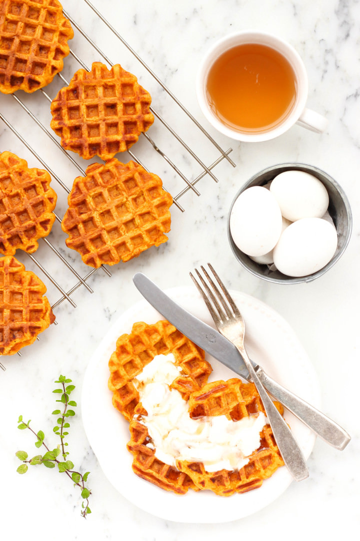 A plate of pumpkin waffles with whipped cream and drizzle in honey.
