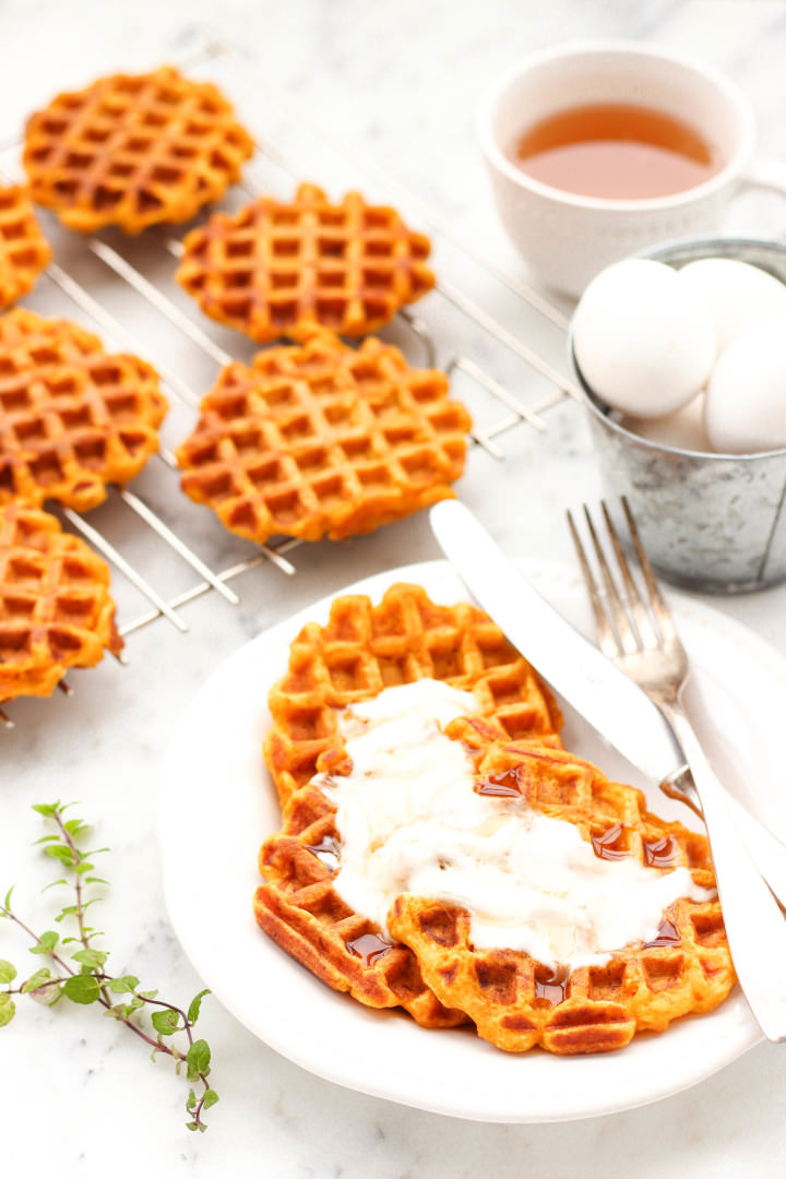 Close up shot of pumpkin waffles with cream and honey.