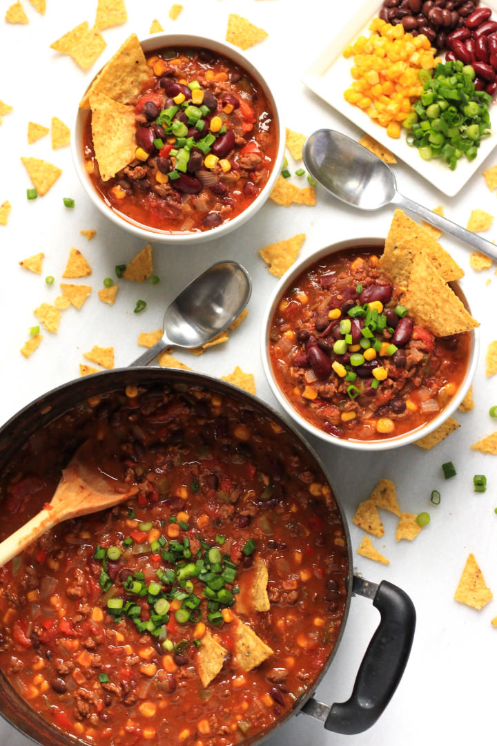 Top down shot of a pot of chili and bowls of chili on a marble board.