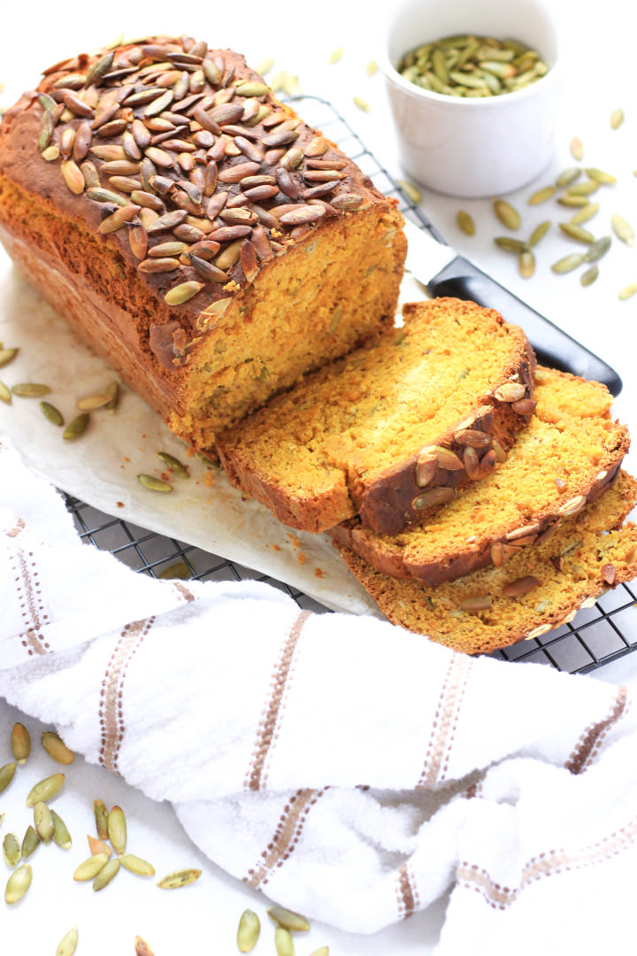 Sliced pumpkin bread surrounded with pumpkin seeds.