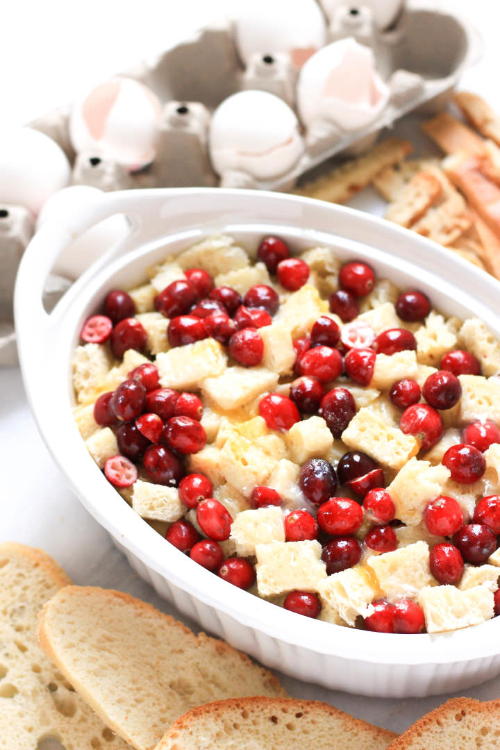 Fresh cranberries and bread cubes in a casserole dish.