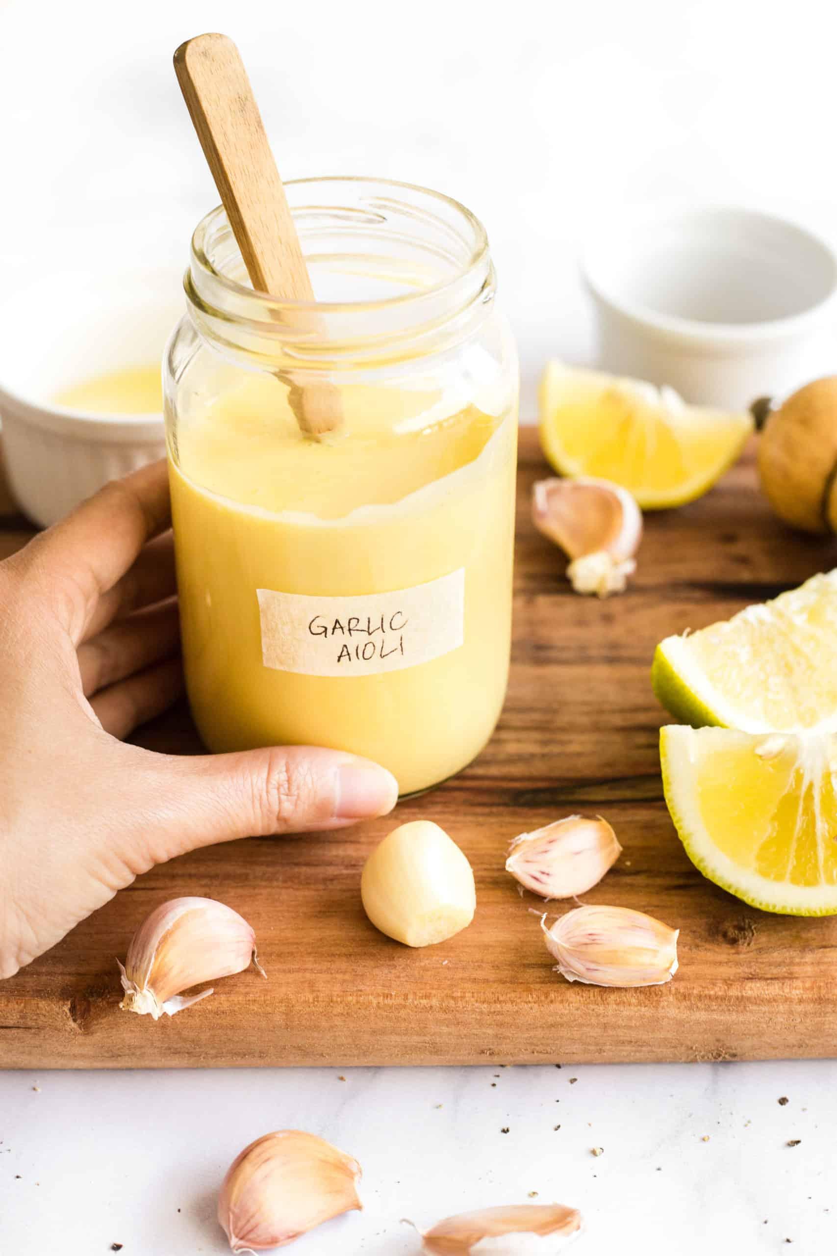 Hand holding a jar of freshly garlic aioli.
