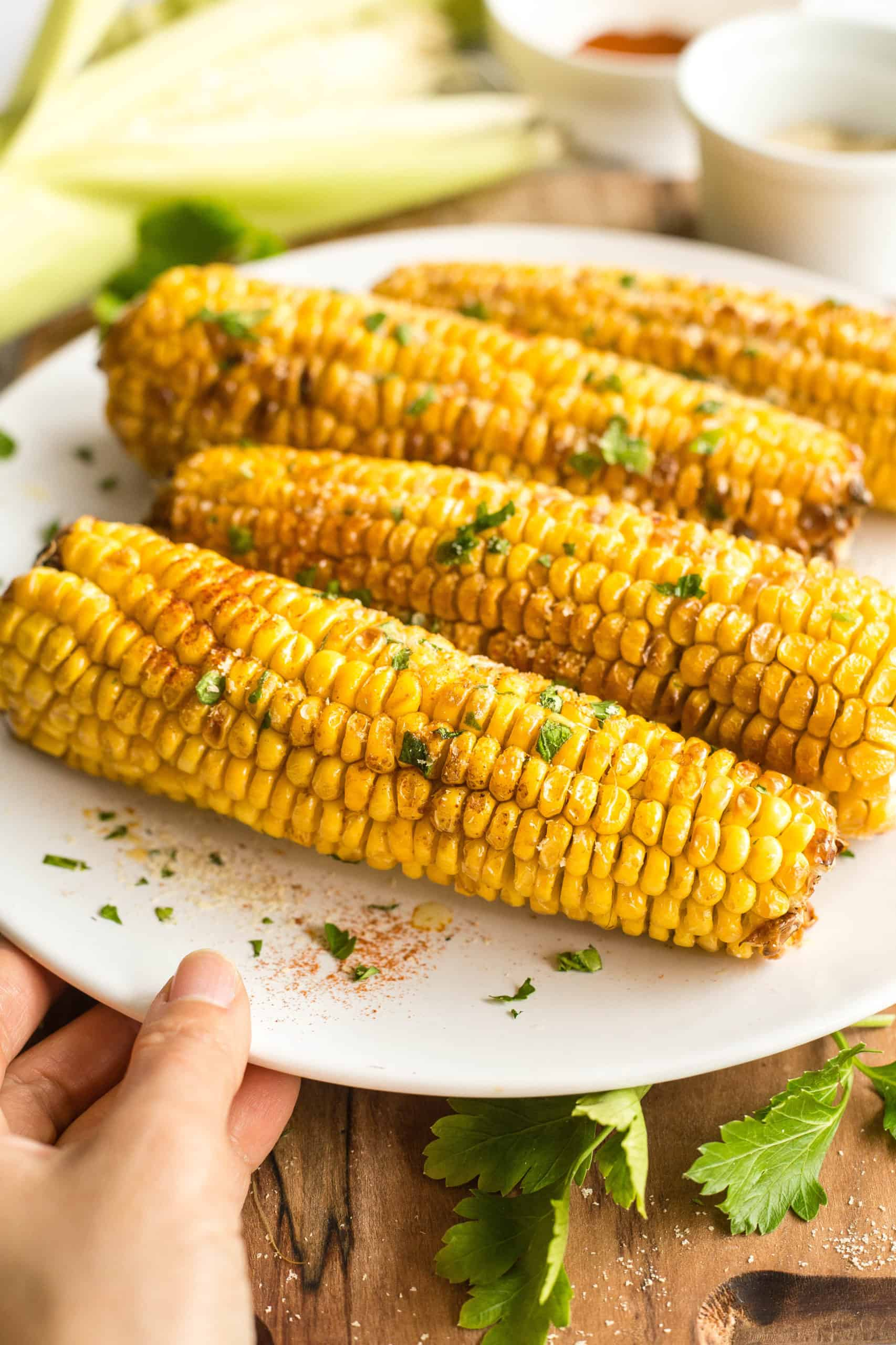 Hand holding a plate of freshly cooked corn on the cob sprinkled with chopped fresh parsley.