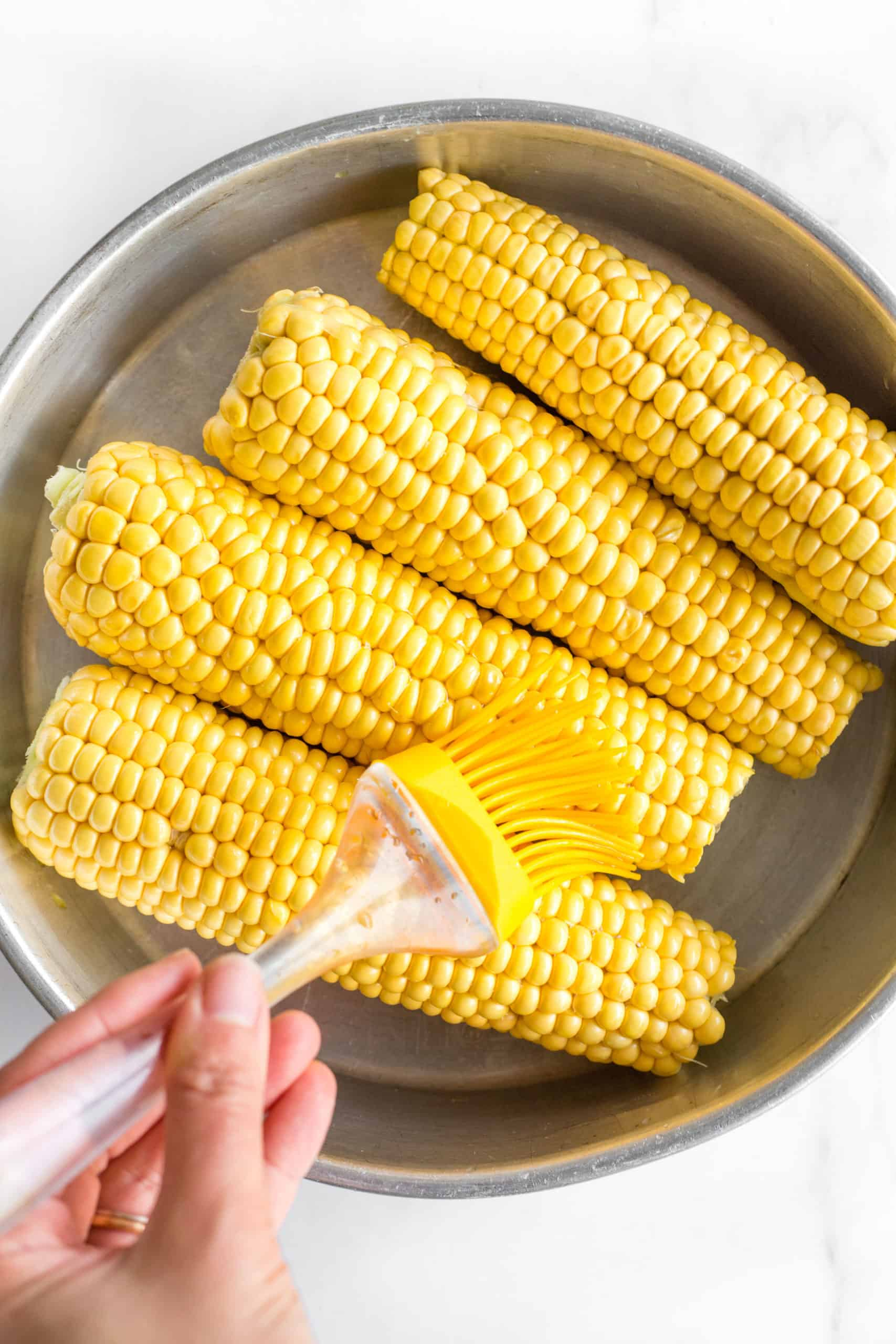 Fresh corn on the cob being brushed with olive oil.