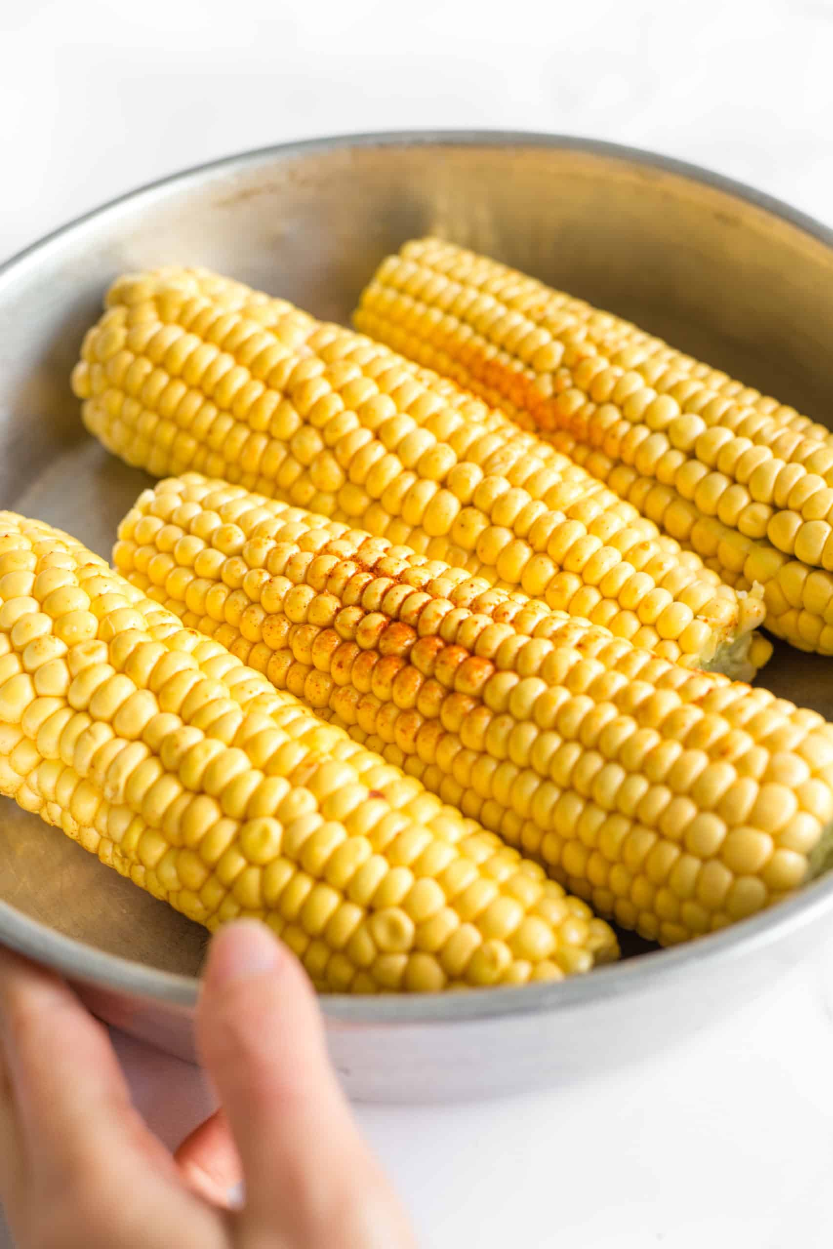 Hand holding a metal bowl of fresh corn on the cob sprinkled with ground paprika.