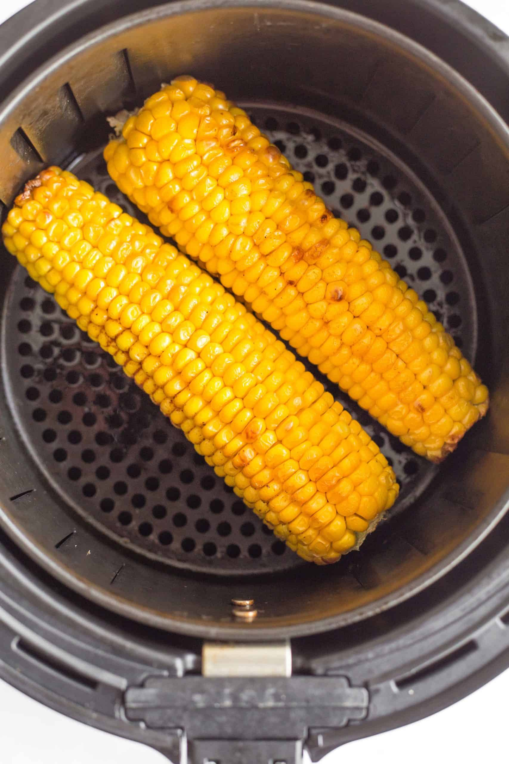 Freshly cooked air fryer corn on the cob in the air fryer basket.