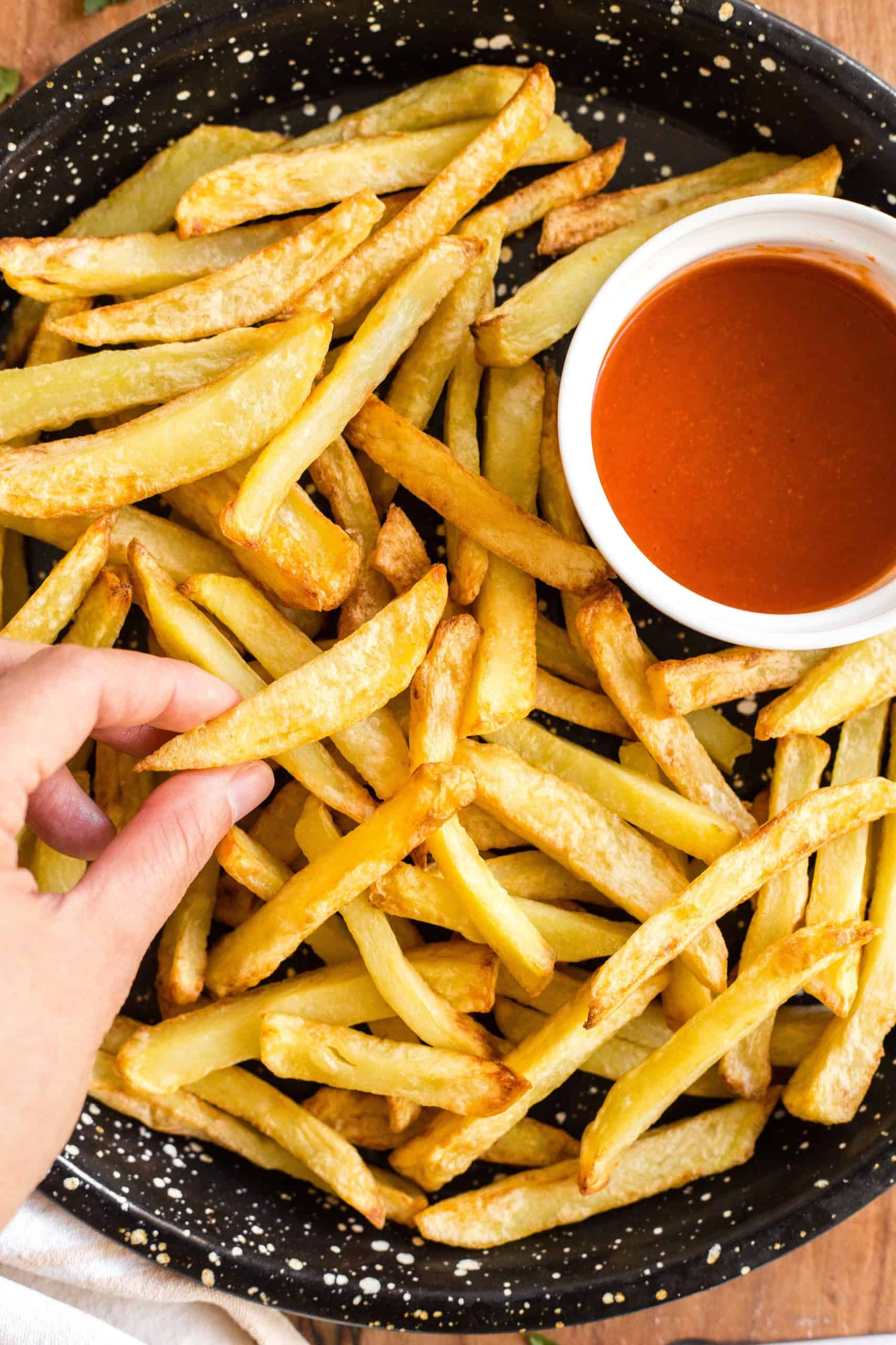 Hand holding a crispy french fry.