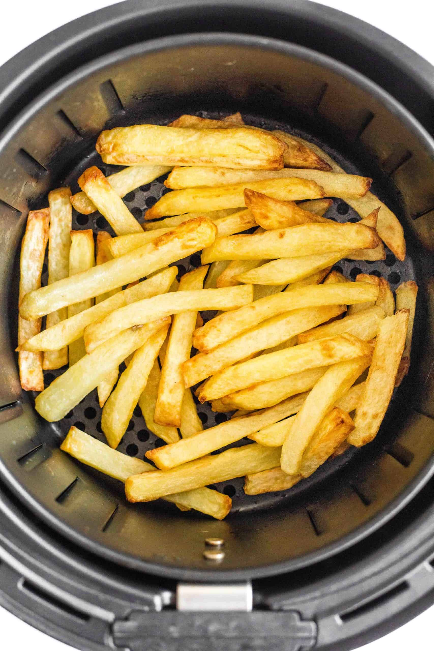Freshly cooked french fries in an air fryer basket.