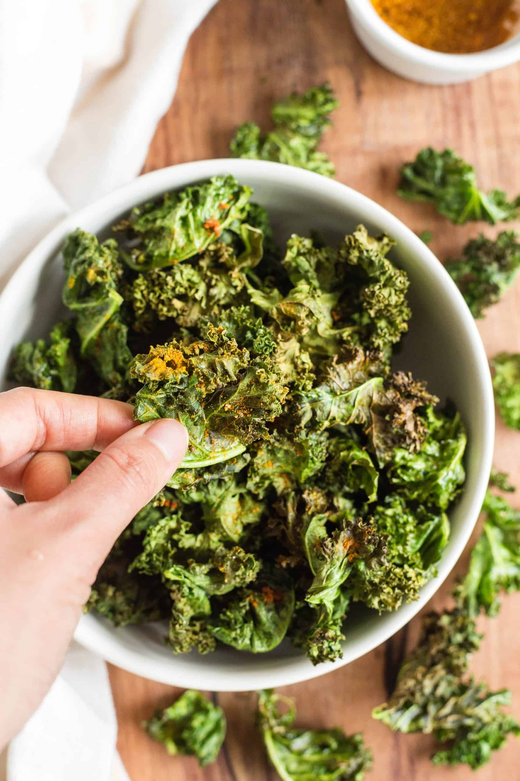 Hand holding up a kale chip from a bowl.
