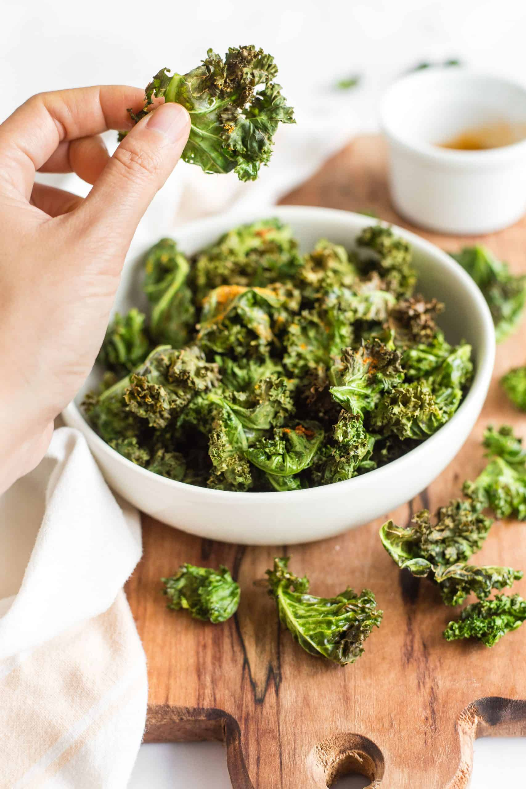 Holding up a kale chip from a bowl.