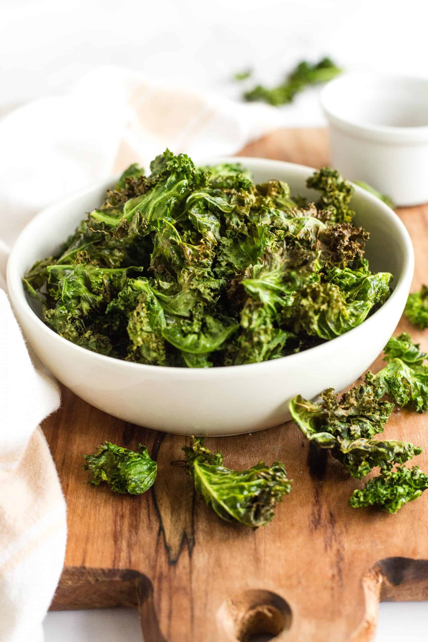 A bowl of kale chips on a wooden board.