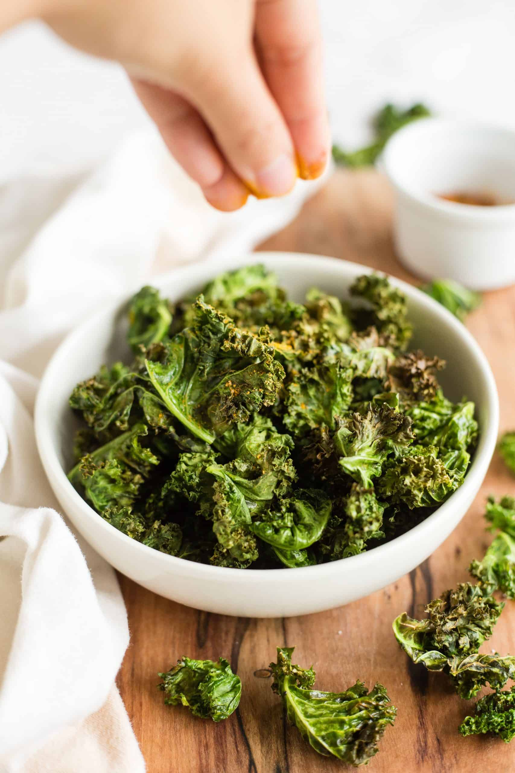 Hand sprinkling spices over a bowl of kale chips.
