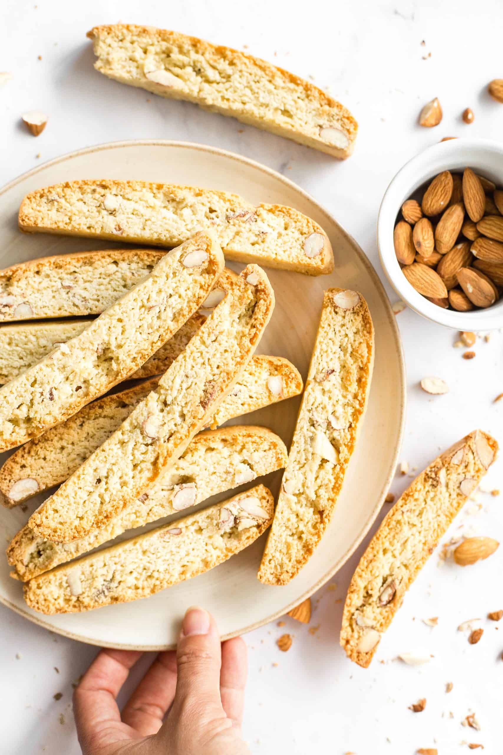 A plate of almond biscotti and raw almonds on a marble board.