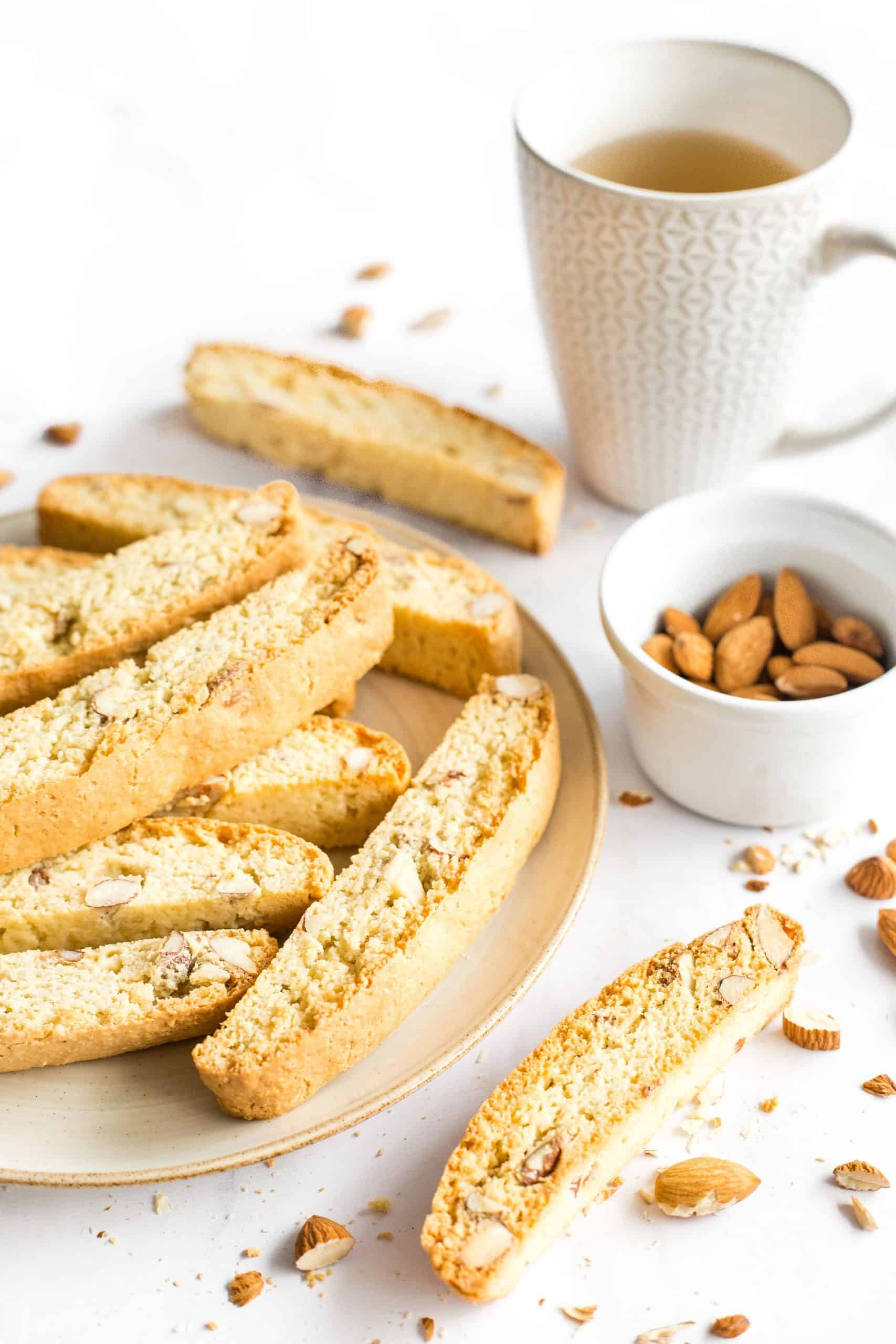 A plate of biscotti, almonds, and a cup of tea on a marble board.