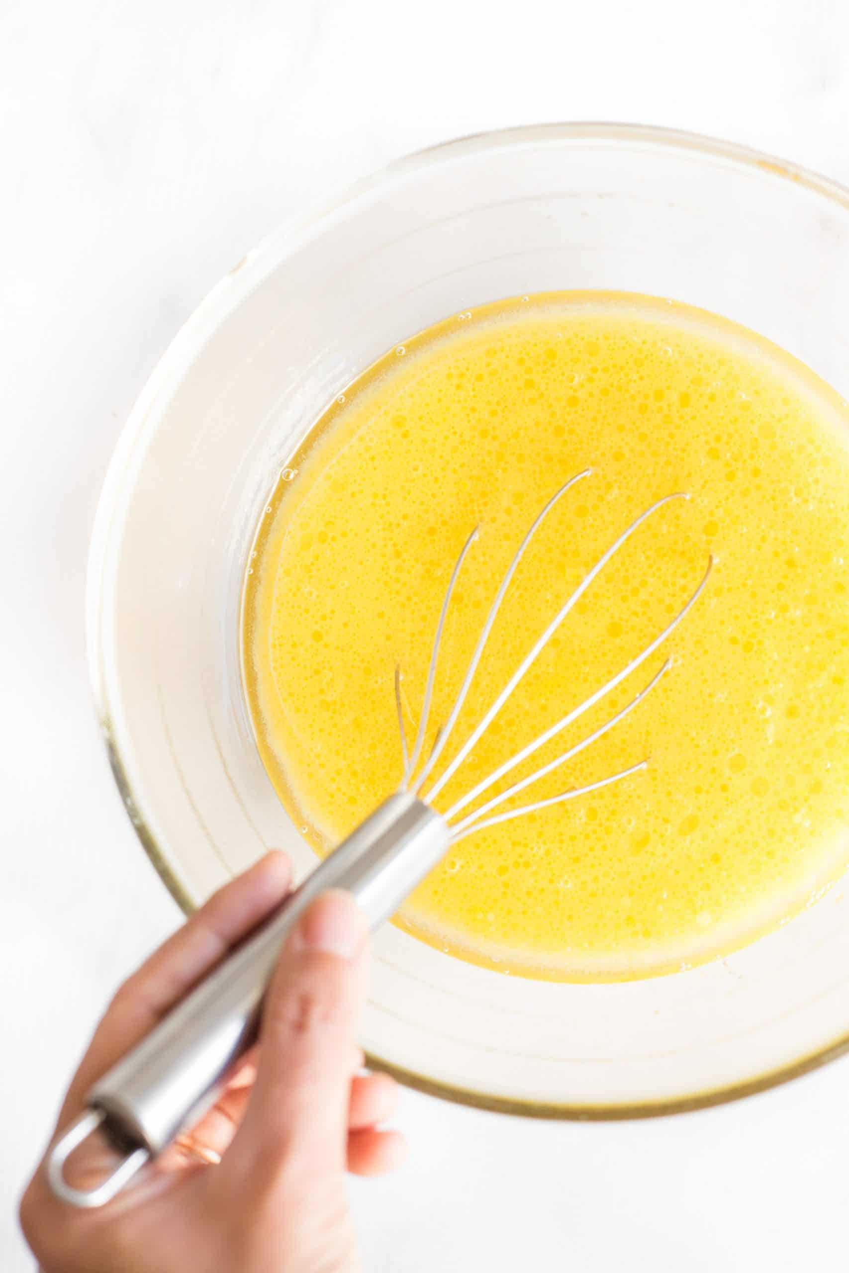 Whisking yellow mixture in a glass mixing bowl.