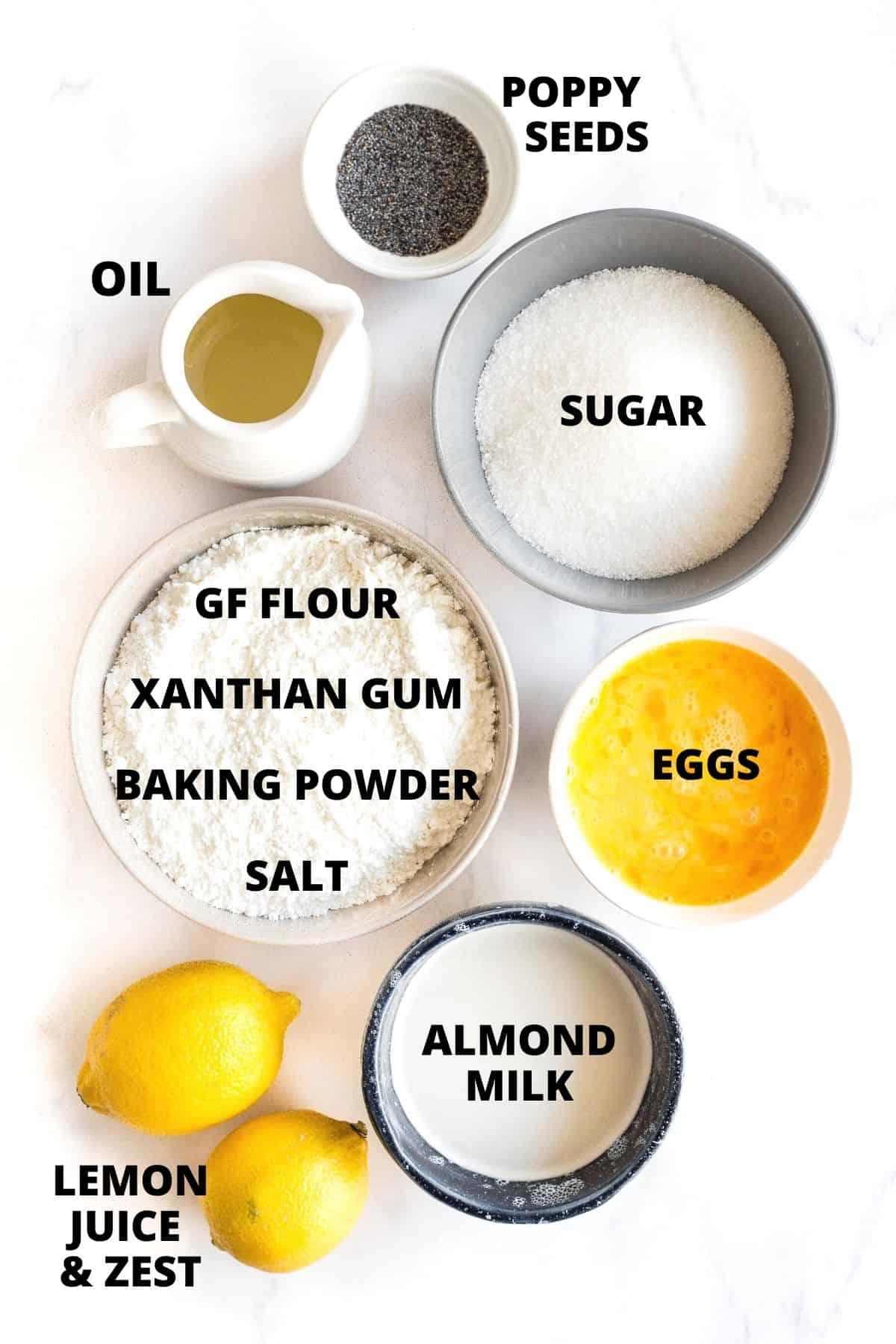 Labeled ingredients for gluten-free lemon poppyseed bread recipe on marble board.