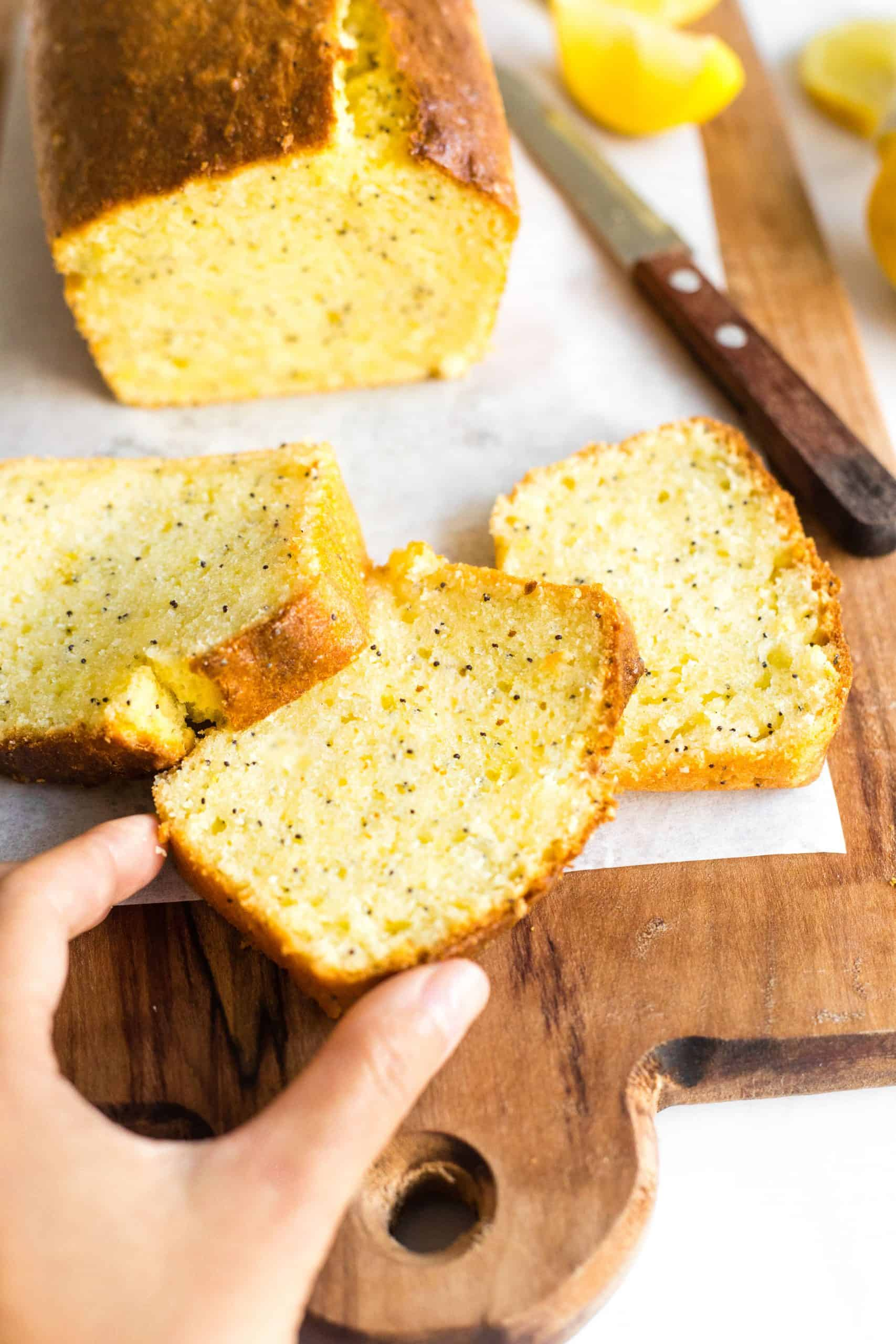 Hand reaching for a slice of gluten-free lemon poppy seed cake.