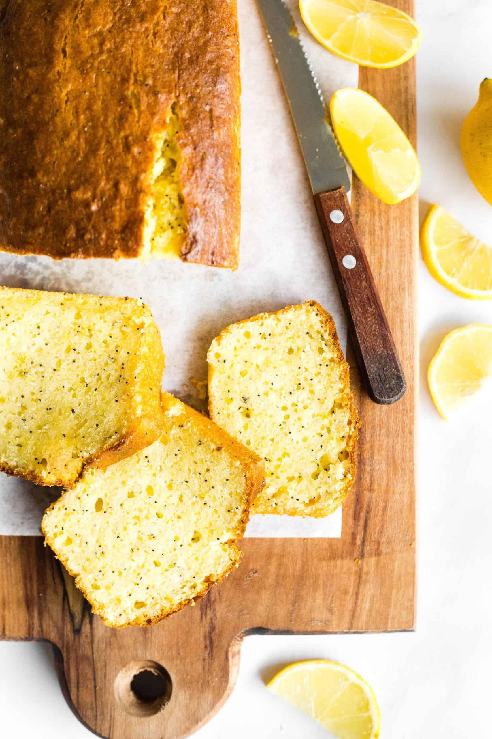 A sliced loaf of gluten-free lemon poppy seed cake on a wooden board.