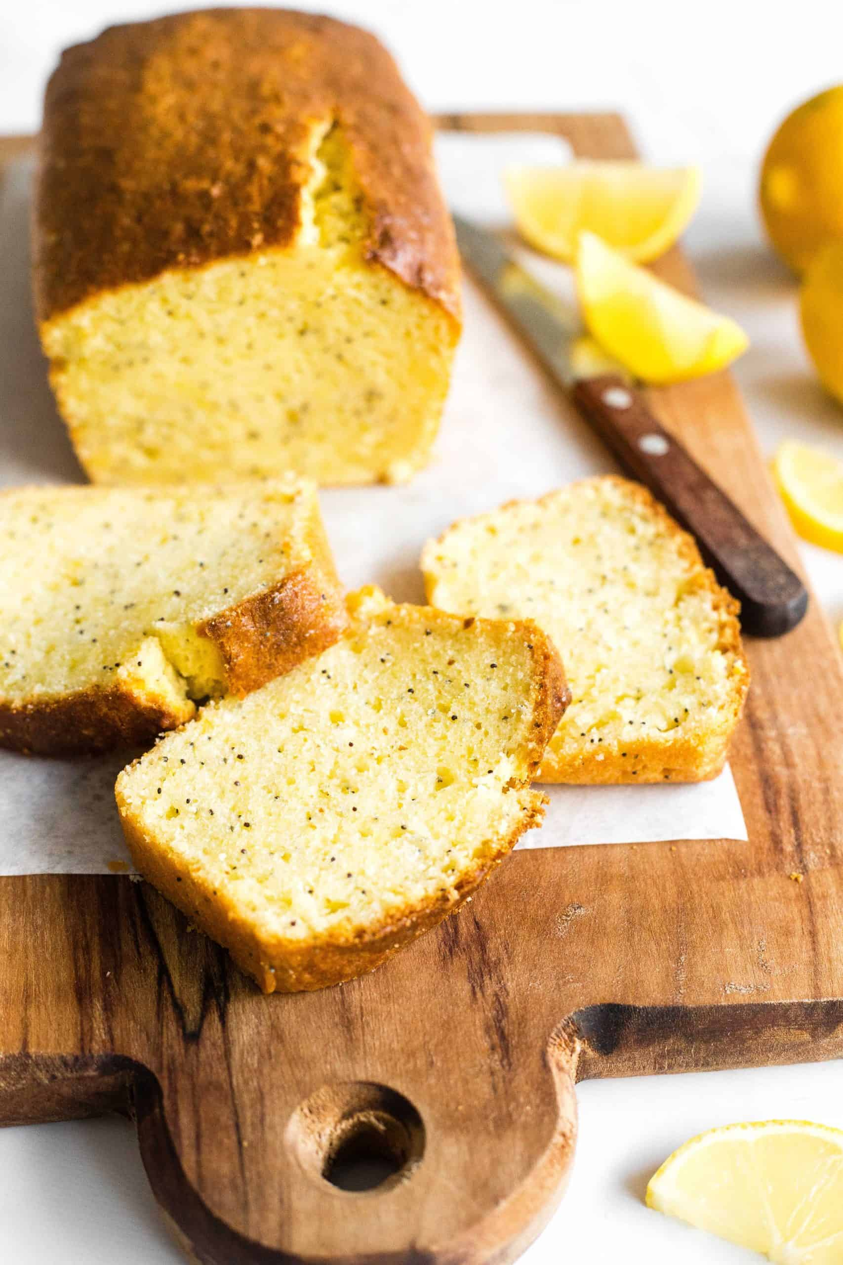 Slices of gluten-free lemon poppy seed cake on a parchment-lined wooden board.