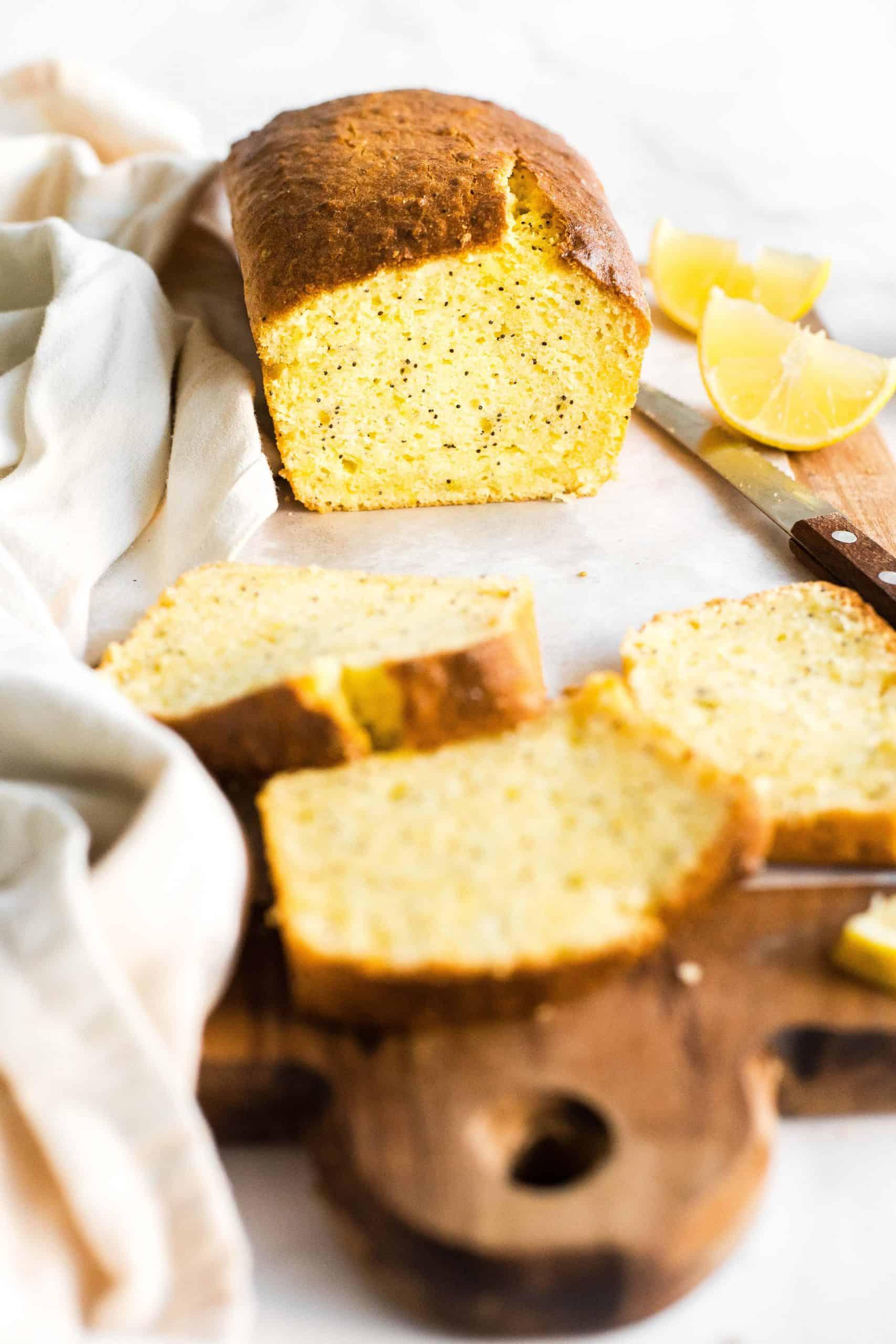 A half-sliced loaf of gluten-free lemon poppyseed bread on a wooden board.