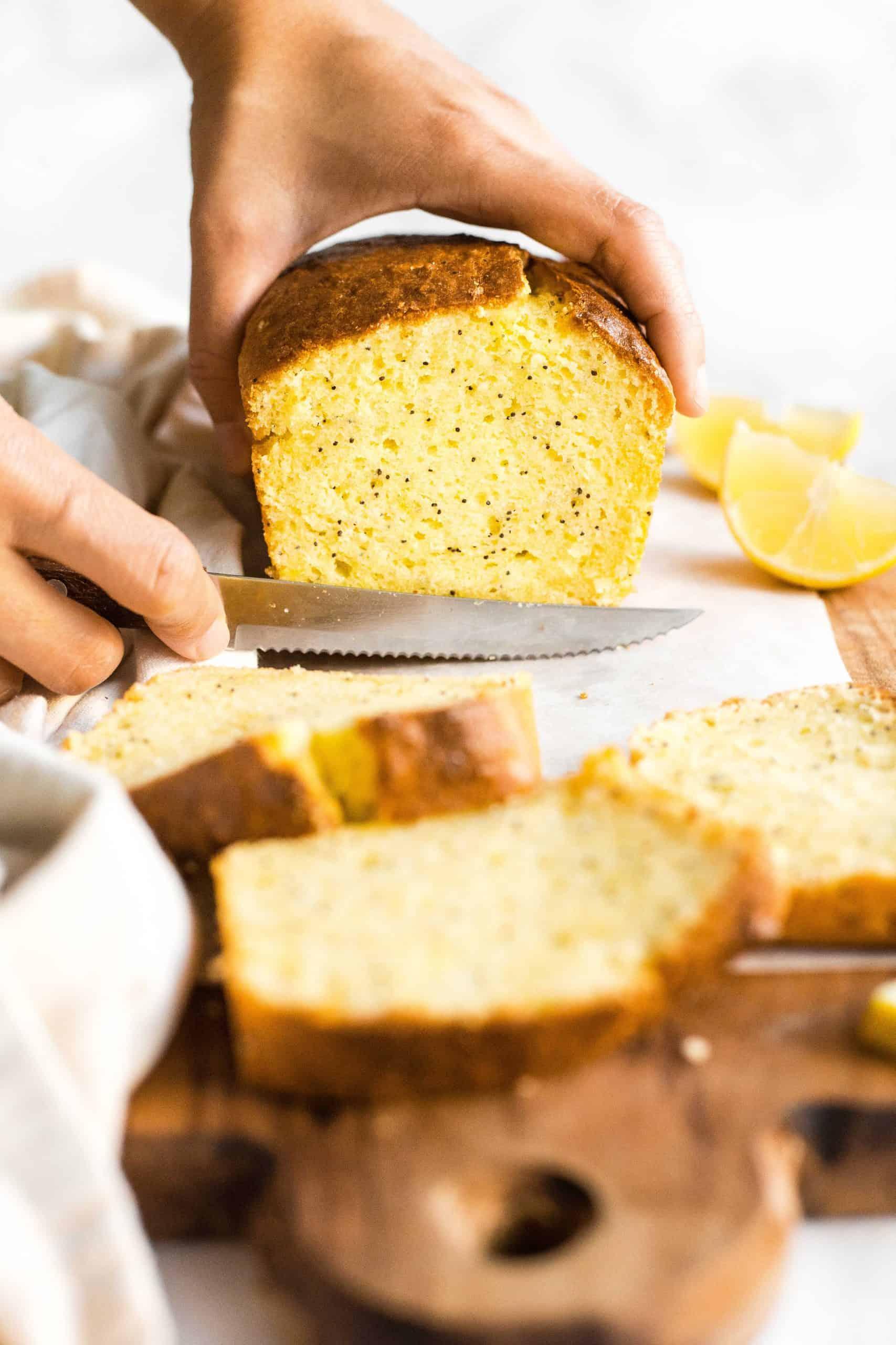 Slicing into a loaf of gluten-free lemon poppyseed bread.