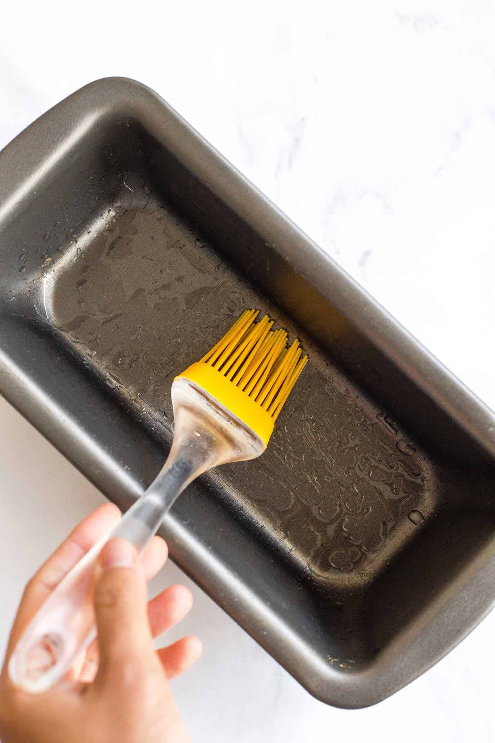 Using a brush to grease a metal loaf pan.
