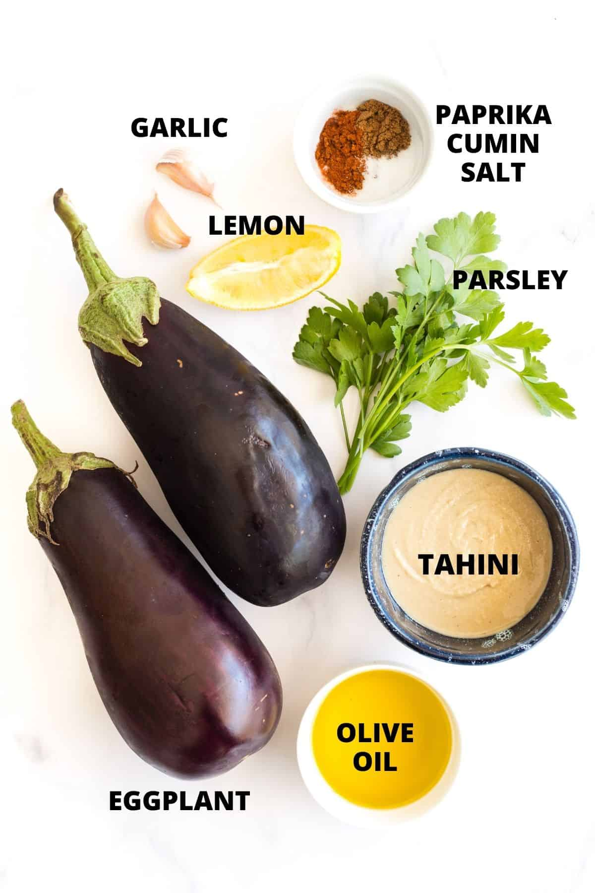Labeled ingredients for baba ganoush recipe laid out on white board.