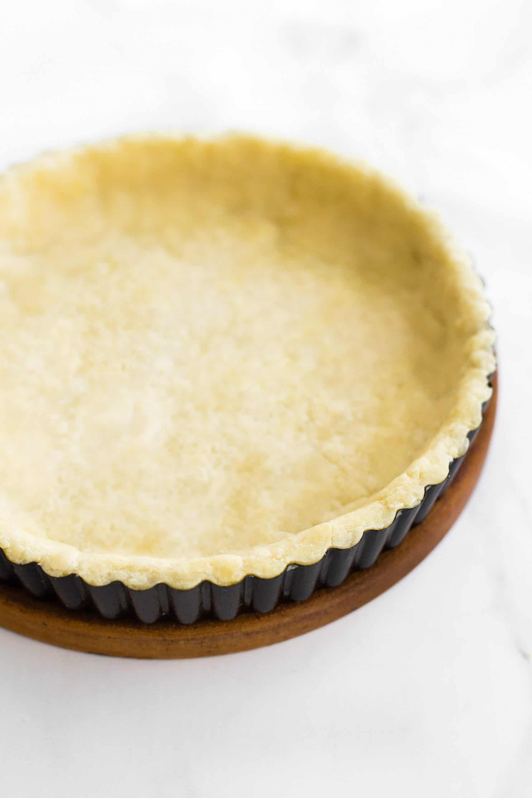 Par-baked pie crust in a pie tin on a wooden board.