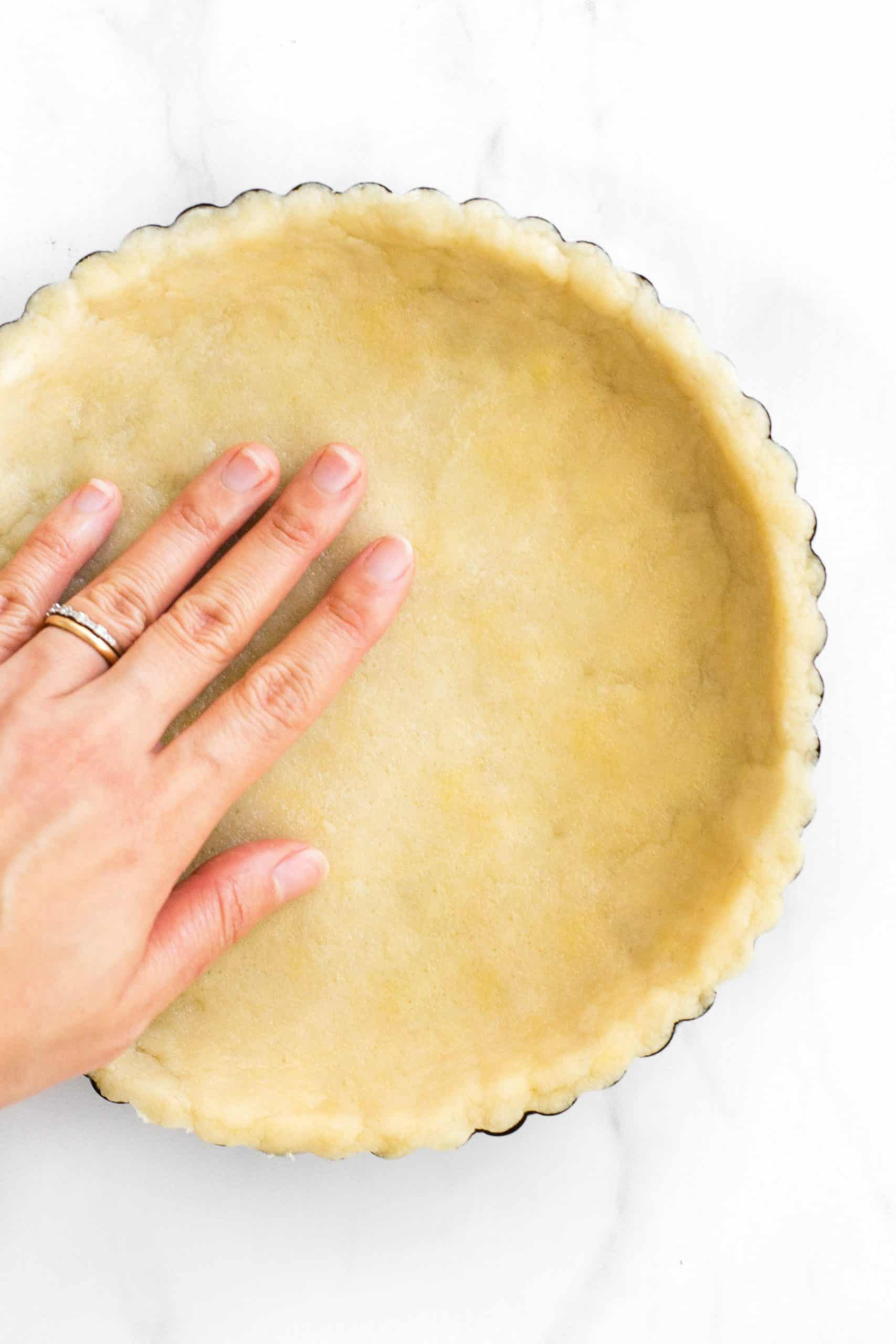 Pressing pie crust dough into a pie pan.