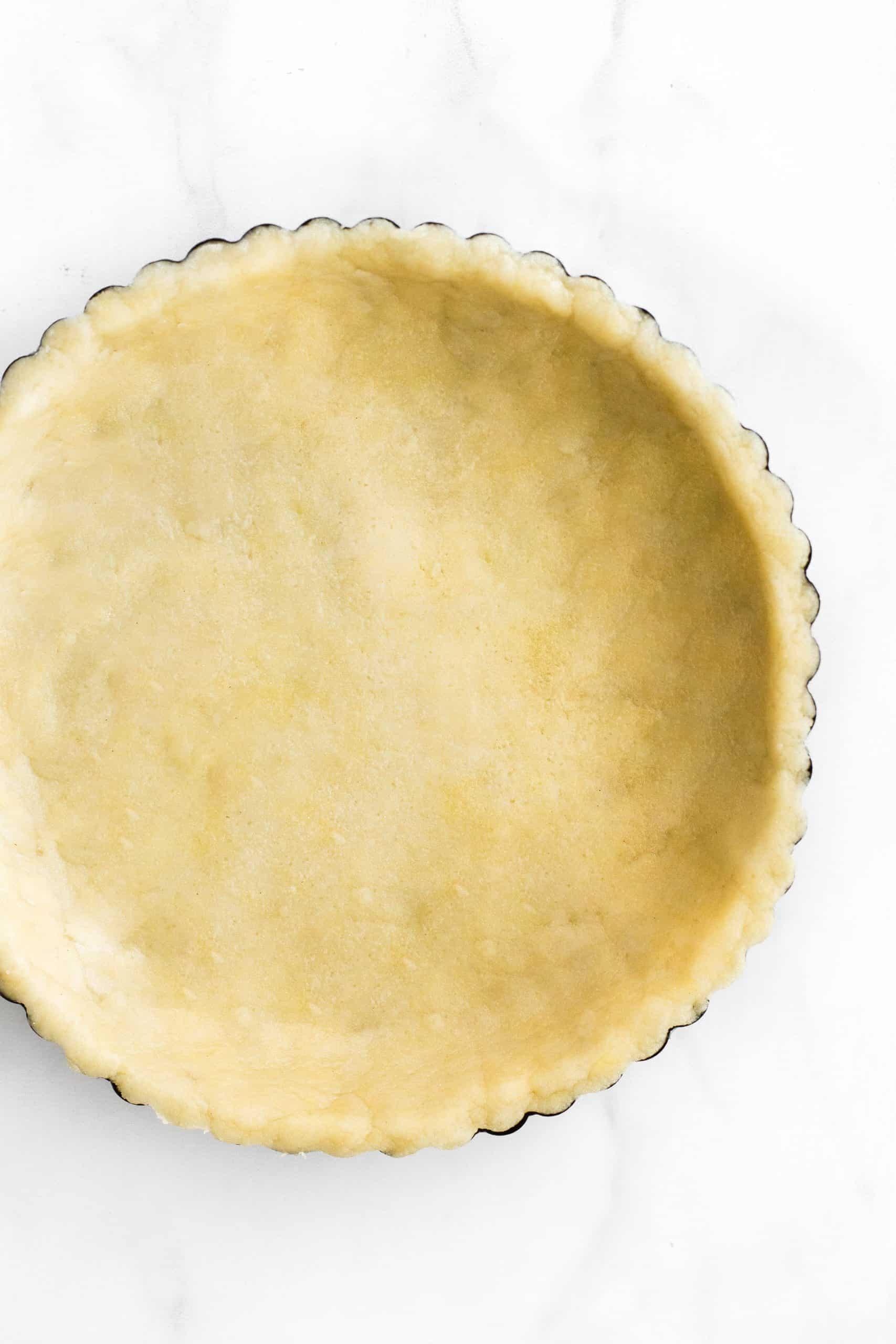 Gluten-free pie crust dough pressed into a metal tin pan.