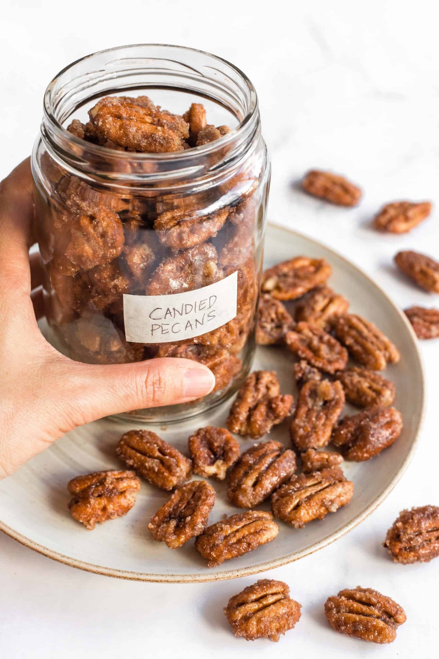 Holding a jar full of candied pecans.