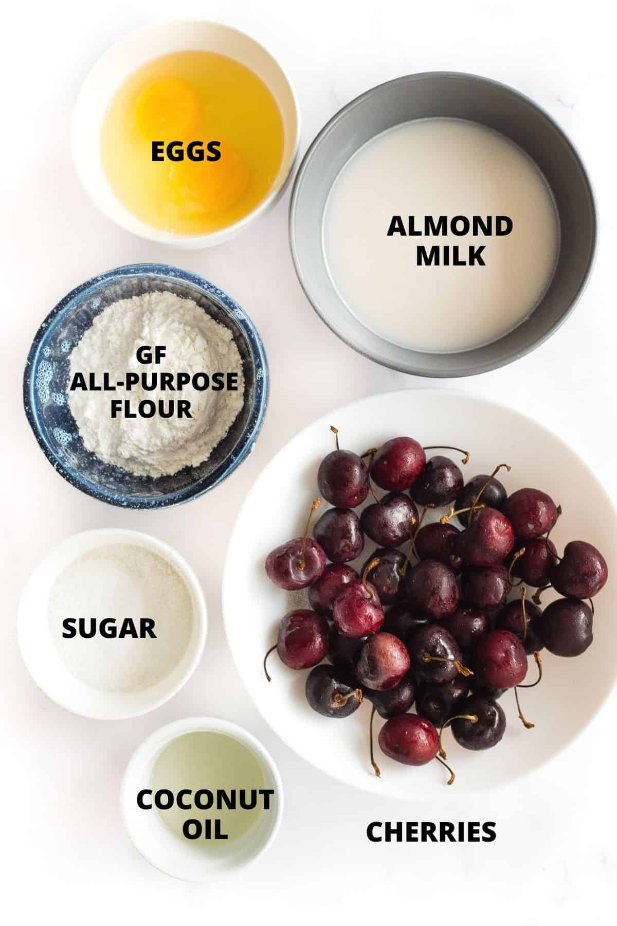 Labeled ingredients for cherry clafoutis recipe laid out on a marble board.