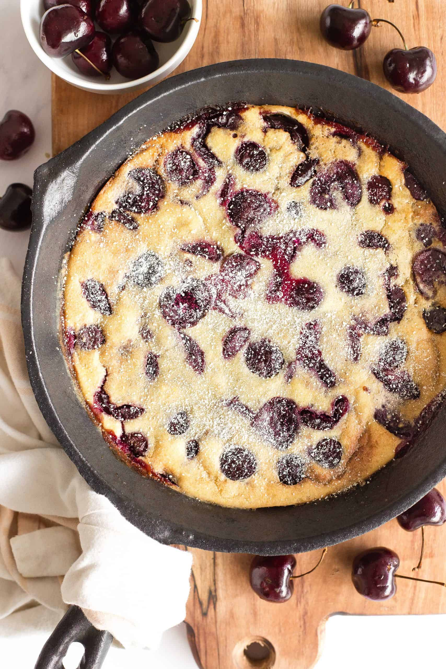 A cast iron skillet with clafoutis on a wooden board.