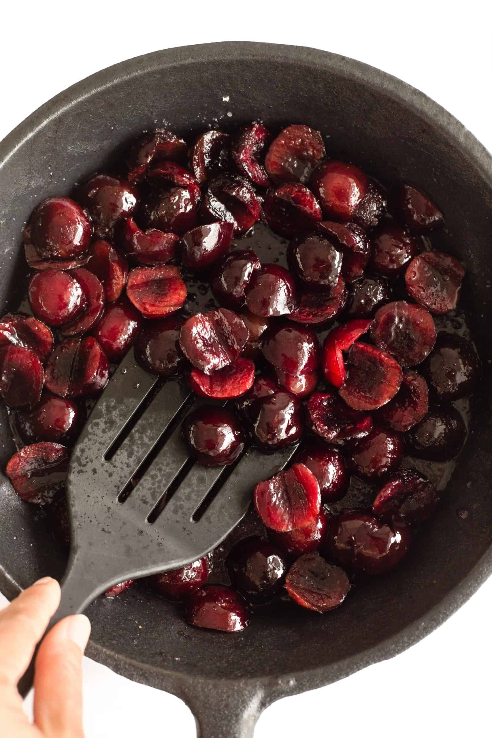 Cooking halved cherries in a cast iron skillet.