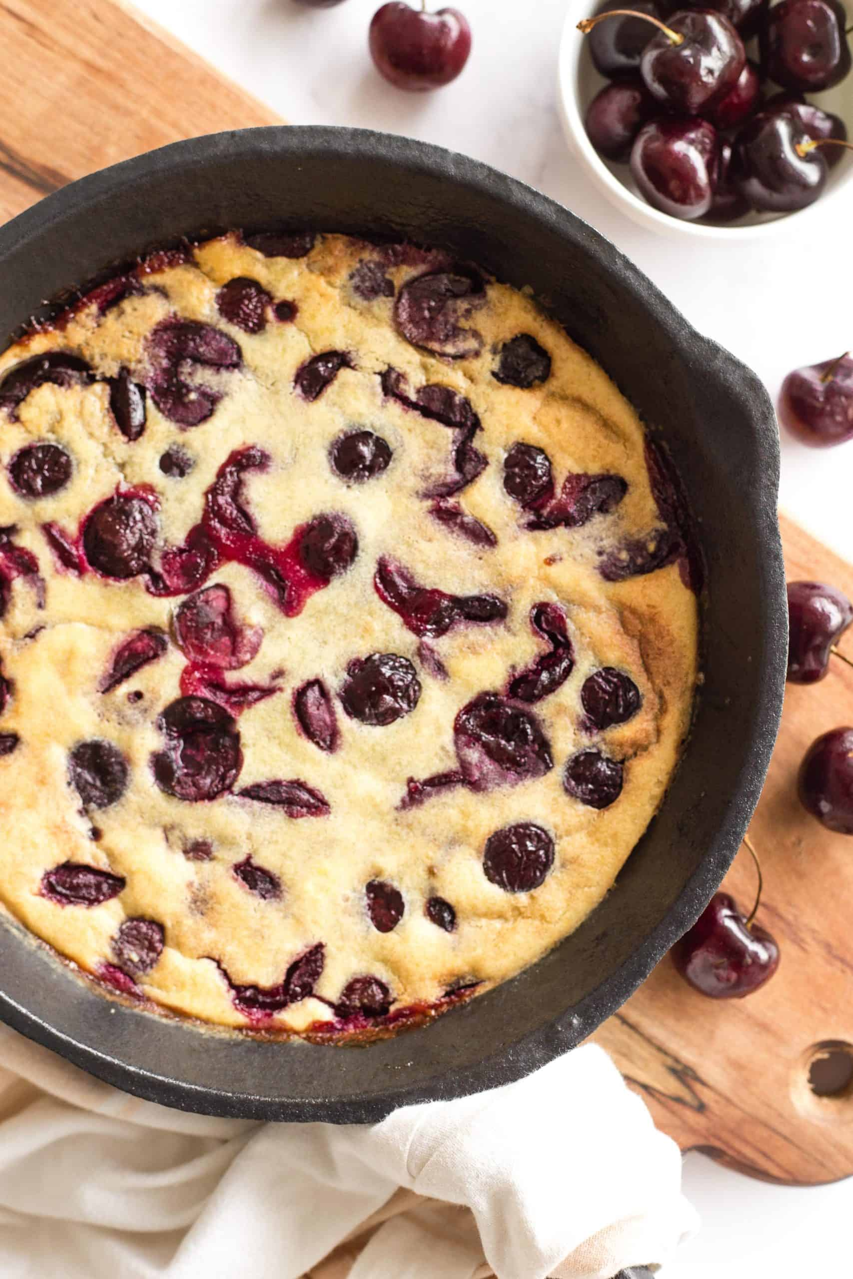 Clafoutis in skillet on a wooden board.