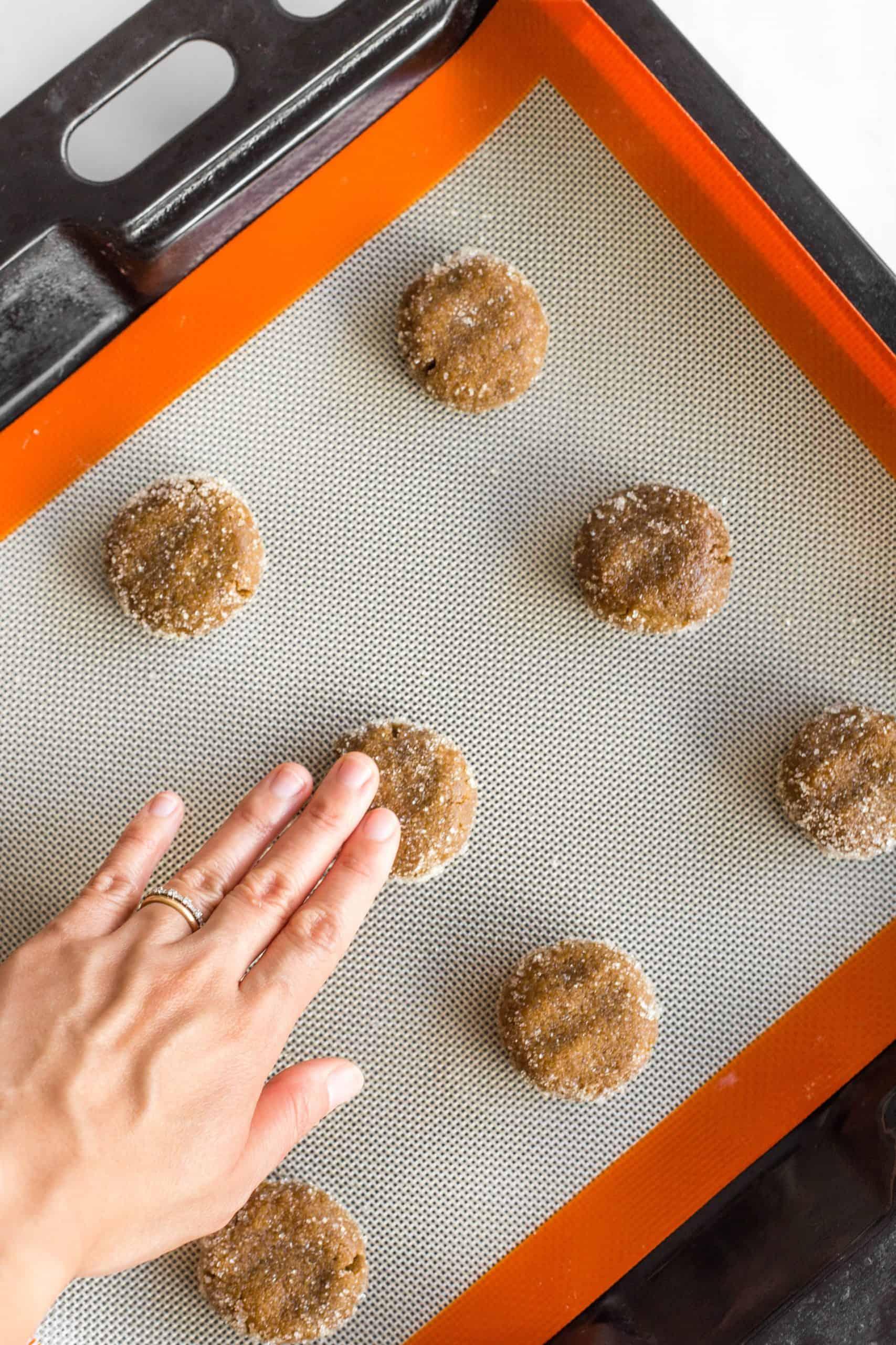 Using fingers to flatten cookie dough balls on a baking sheet.