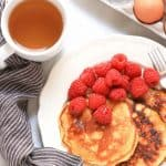 A plate of pancakes and raspberries