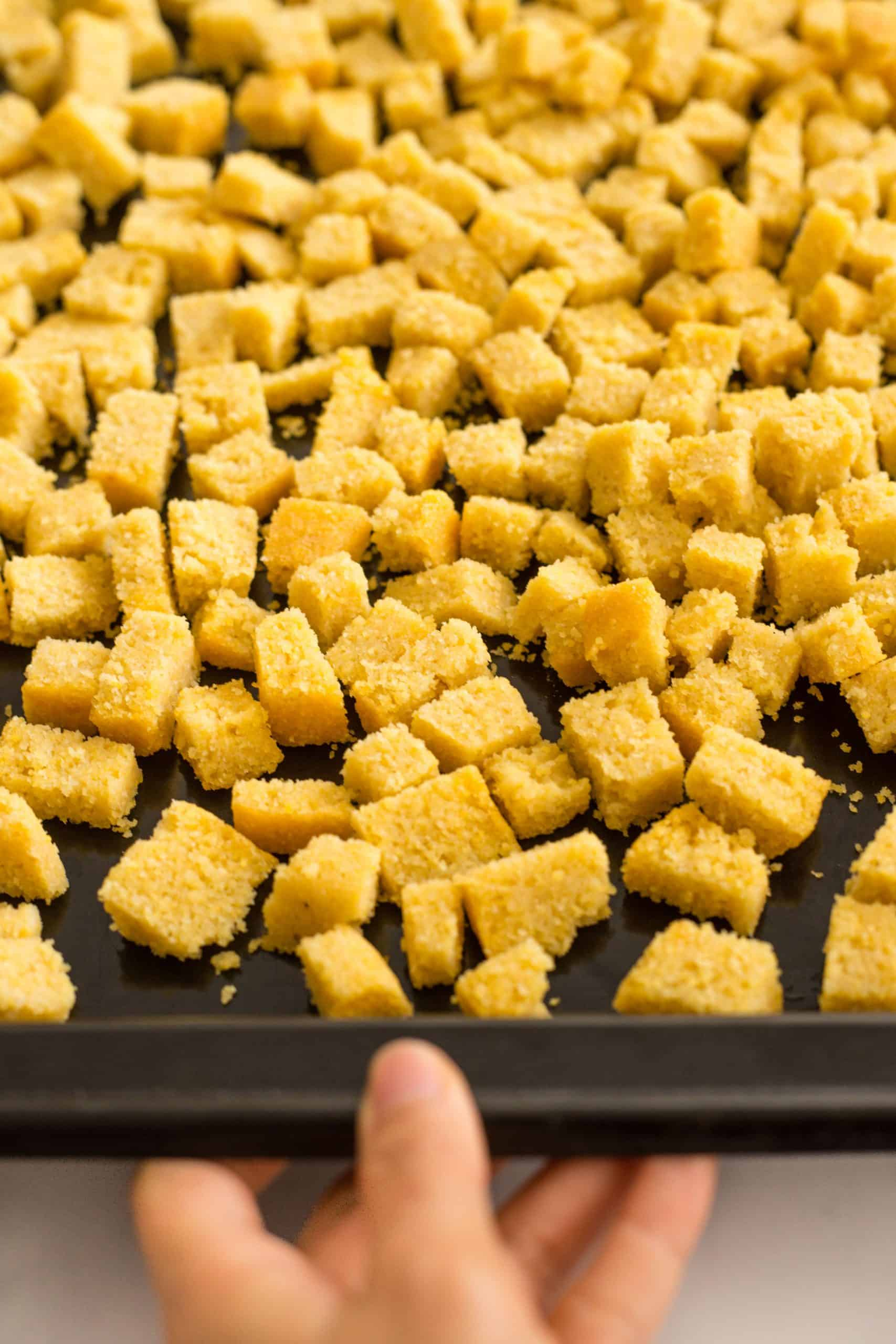 Hand holding a baking pan full of cubed cornbread.
