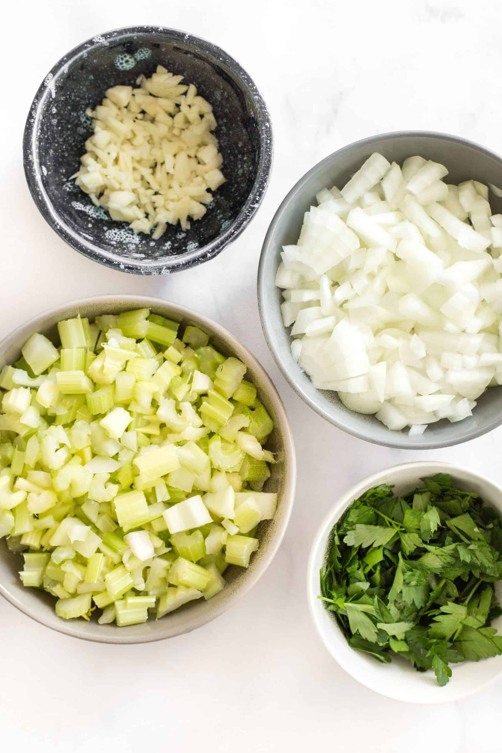 Chopped vegetables in bowls on a white marble board.