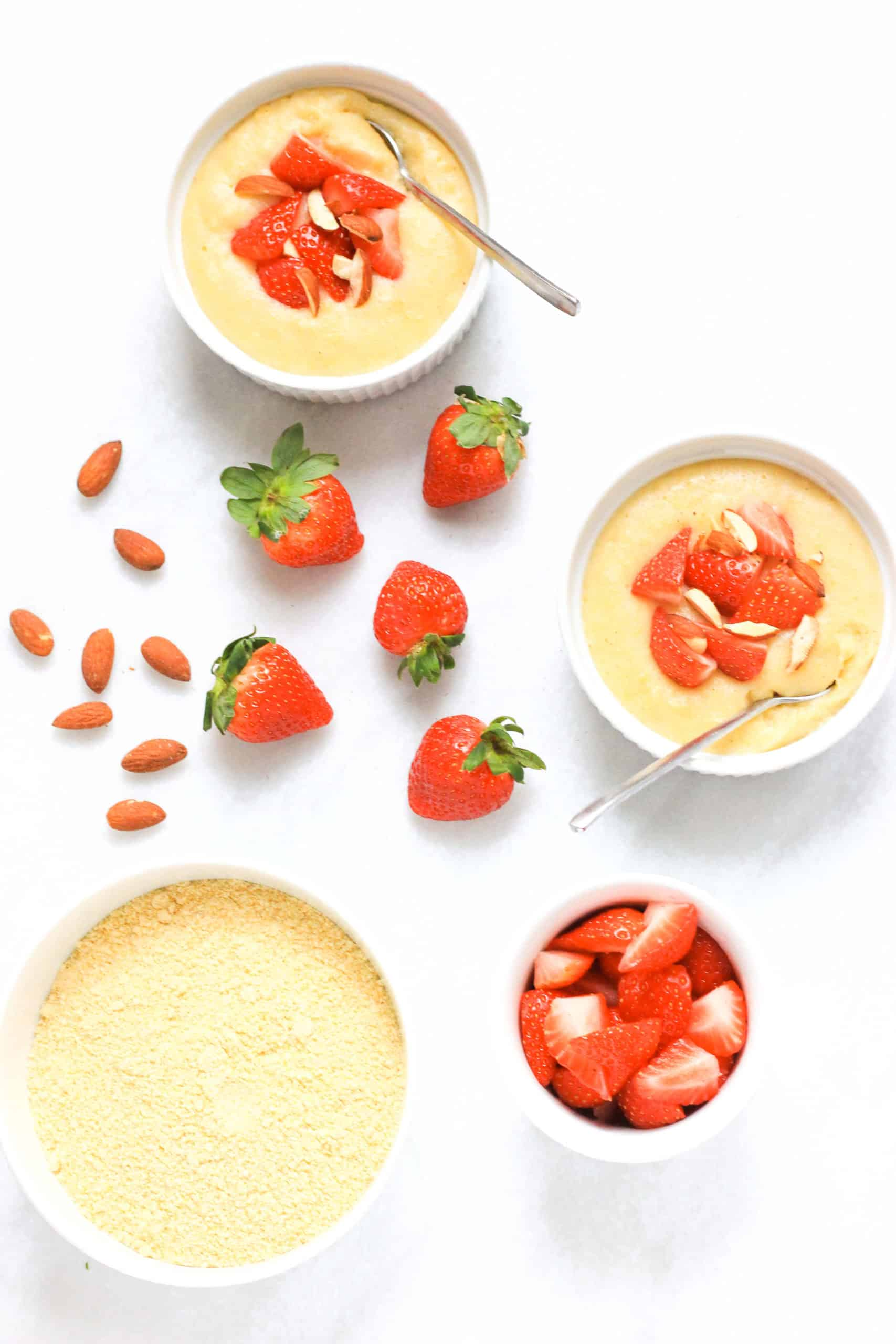 Bowls of creamy breakfast polenta topped with strawberries and almonds.