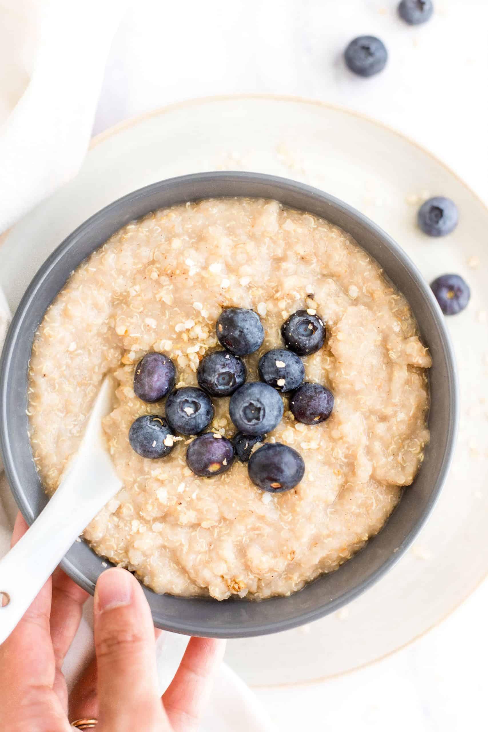 A bowl of creamy quinoa porridge with fresh blueberries.