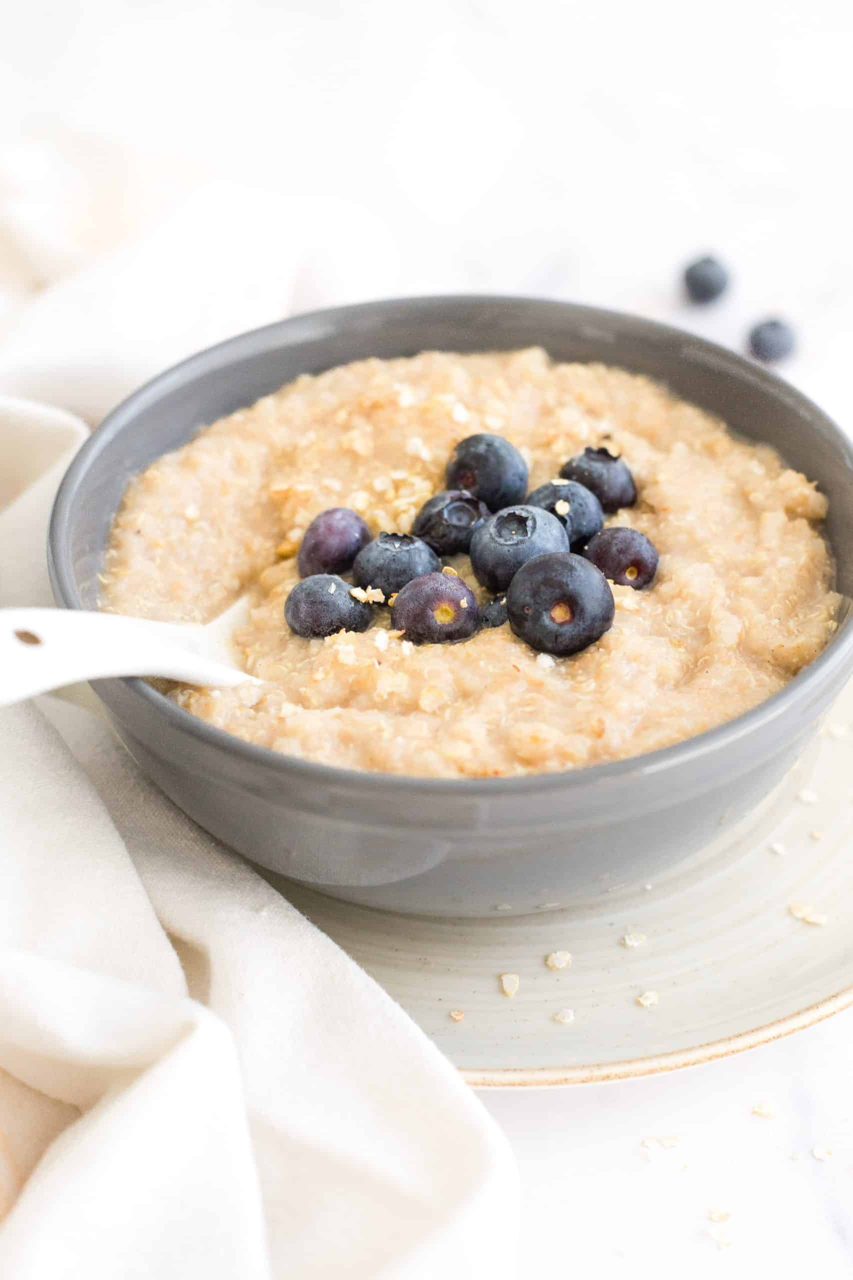 A spoon in a bowl of porridge with blueberries.