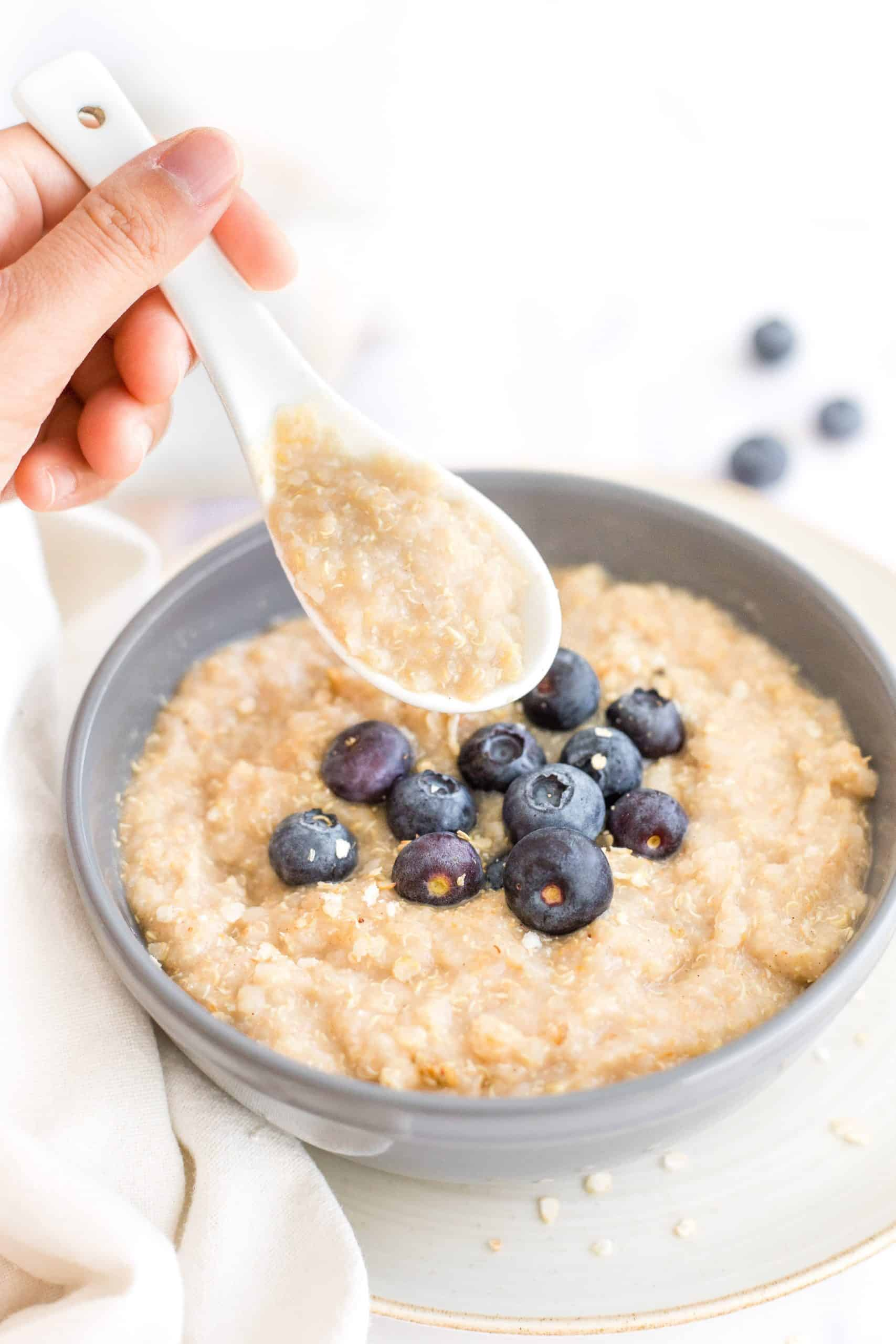 Holding up a spoonful of quinoa porridge from a bowl.