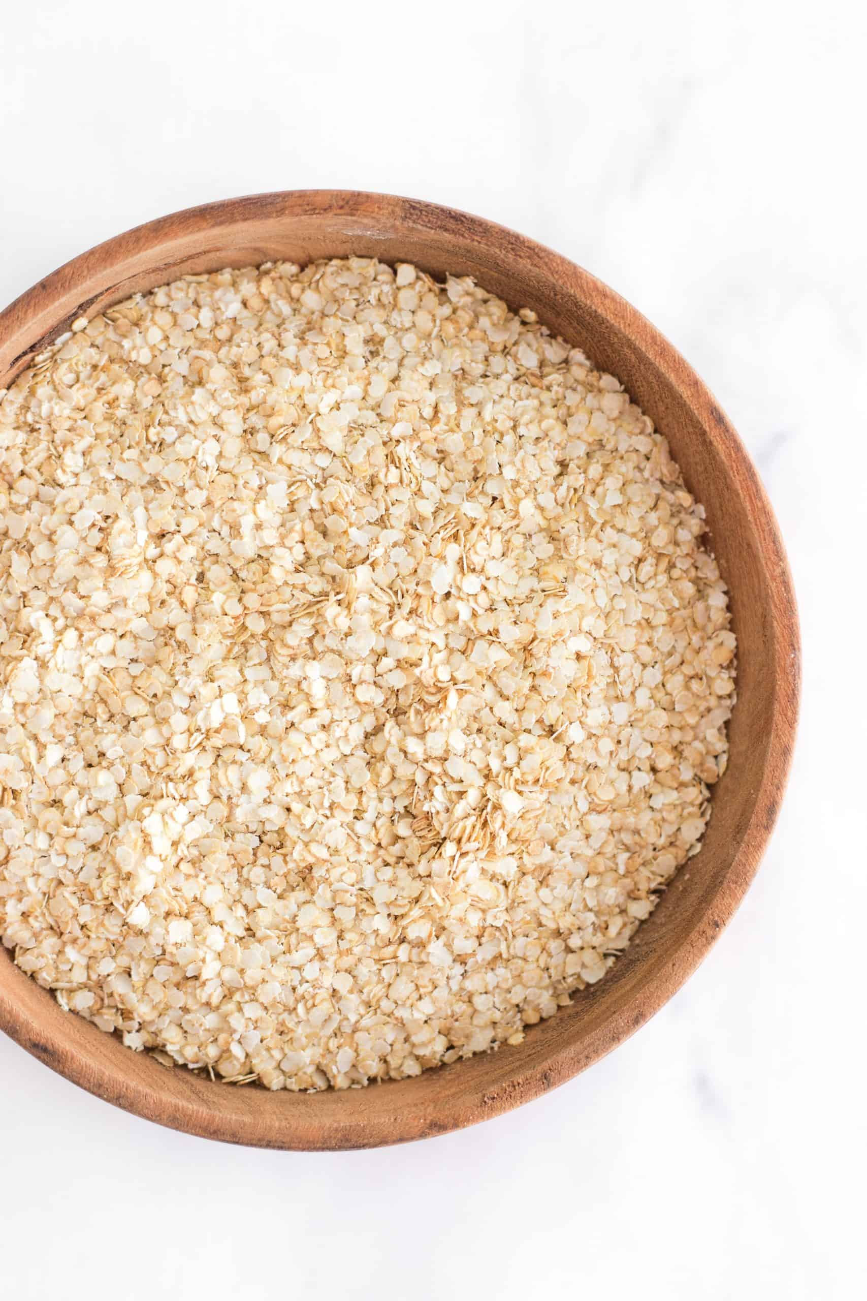 Quinoa flakes in a wooden bowl.