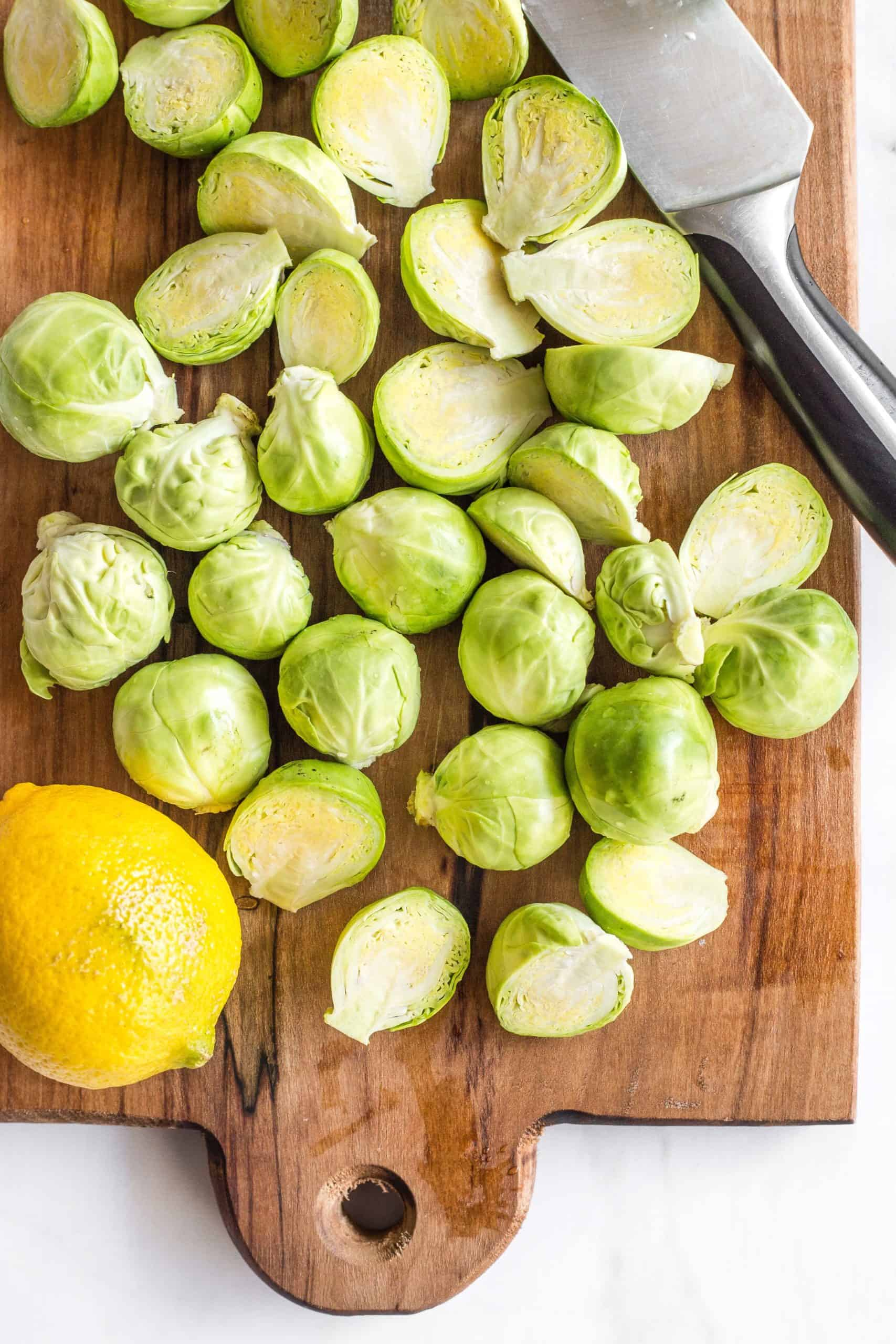 Raw Brussels sprouts cut into halves on a wooden board.